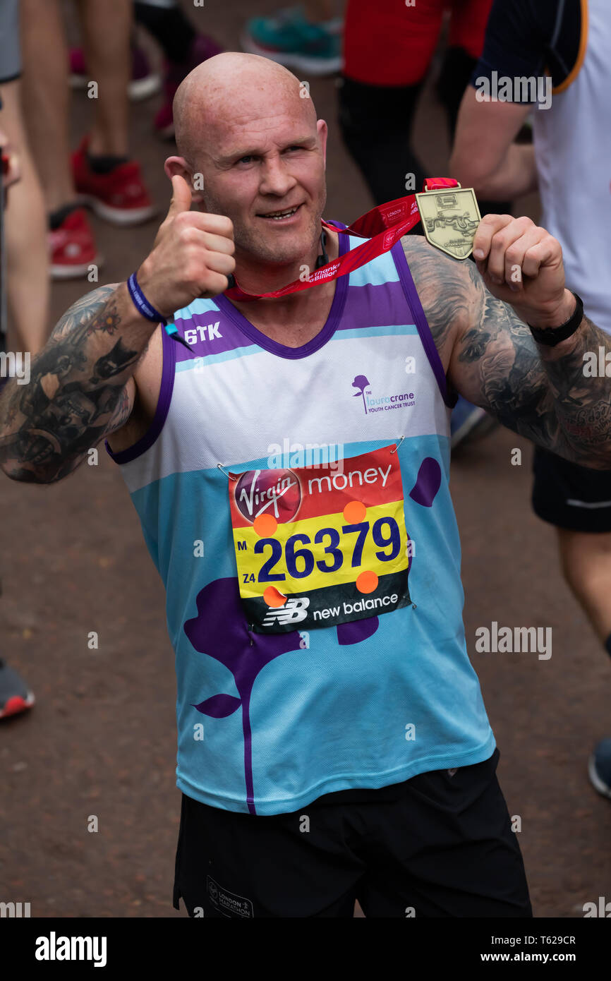 London, UK. 28th April 2019. Keith Senior, English former rugby player with his medal after completing The 39th London Marathon. Credit: Keith Larby/Alamy Live News Stock Photo