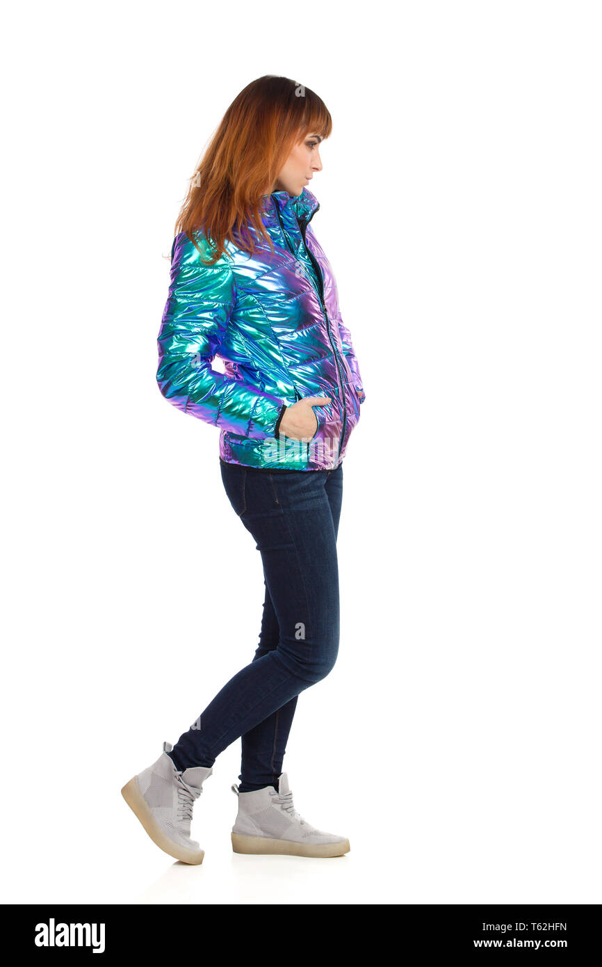 Skeptic young woman in vibrant and shiny down jacket, jeans and sneakers is standing with hands in pockets and looking away. Side view. Full length st - Stock Image
