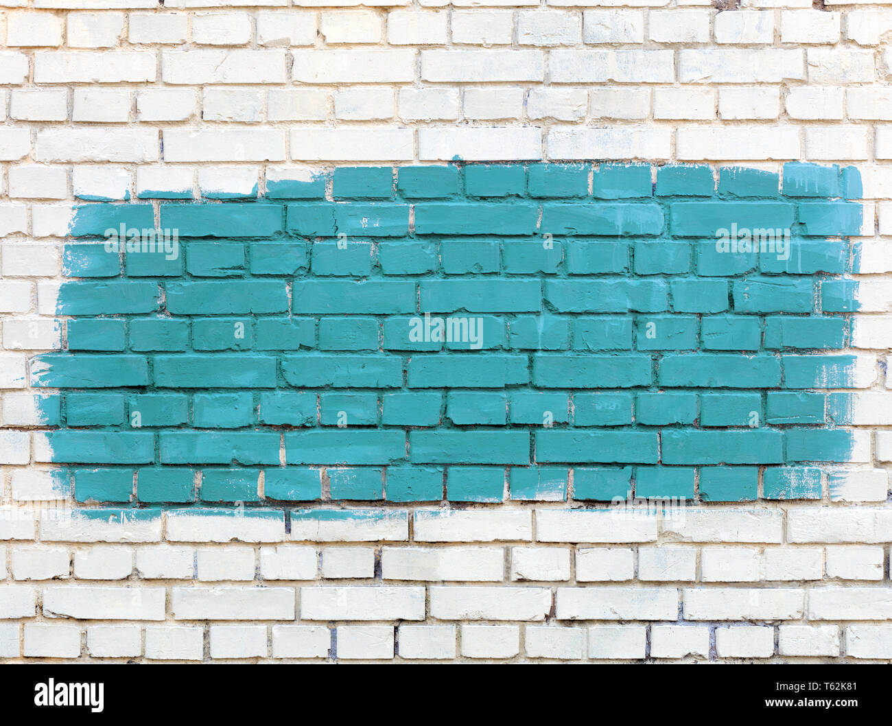 The old walls are painted with white paint and the selected fragment is painted with green paint. - Stock Image
