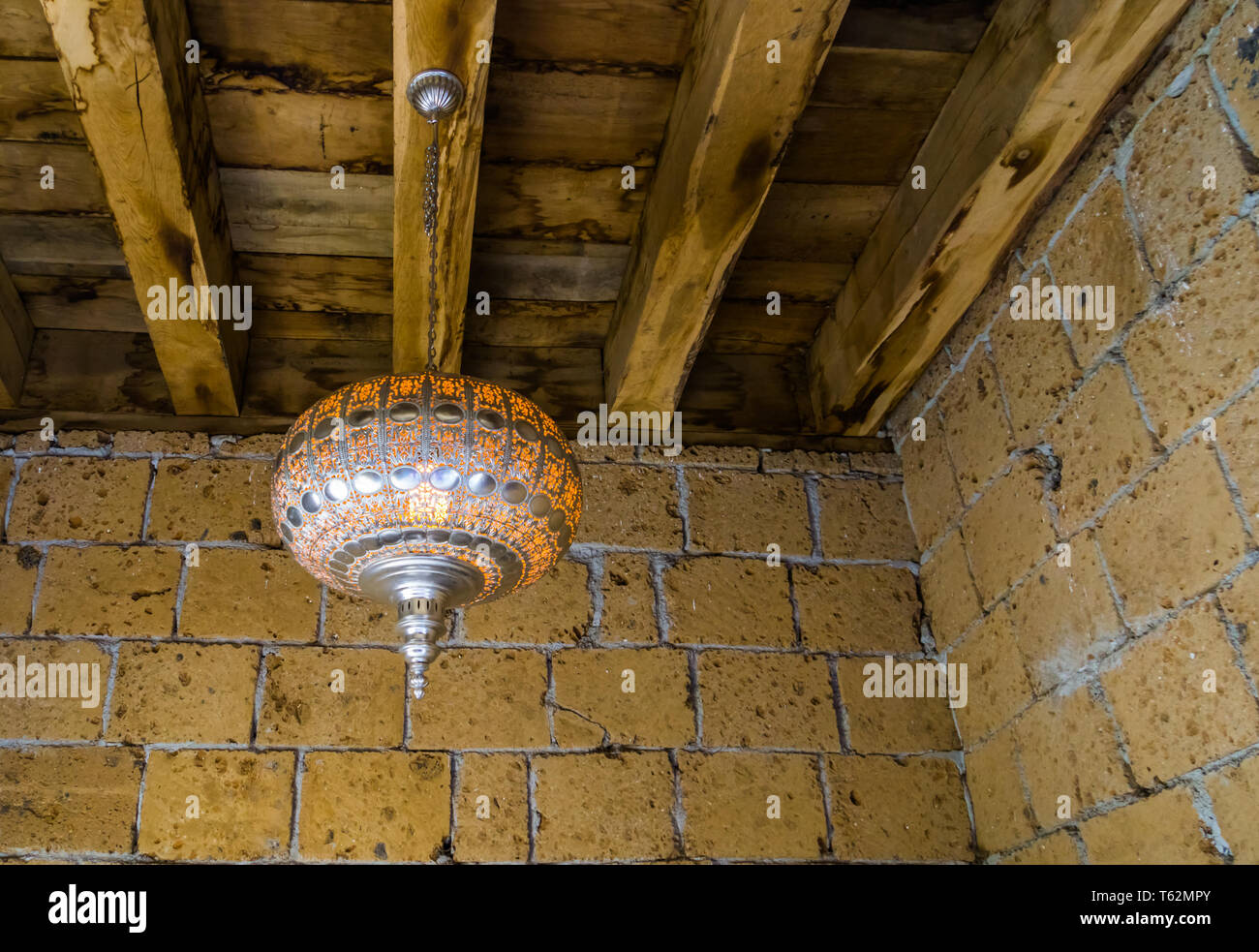 Silver moroccan lighted lantern hanging on a wooden roof, traditional home interiors and decorations - Stock Image