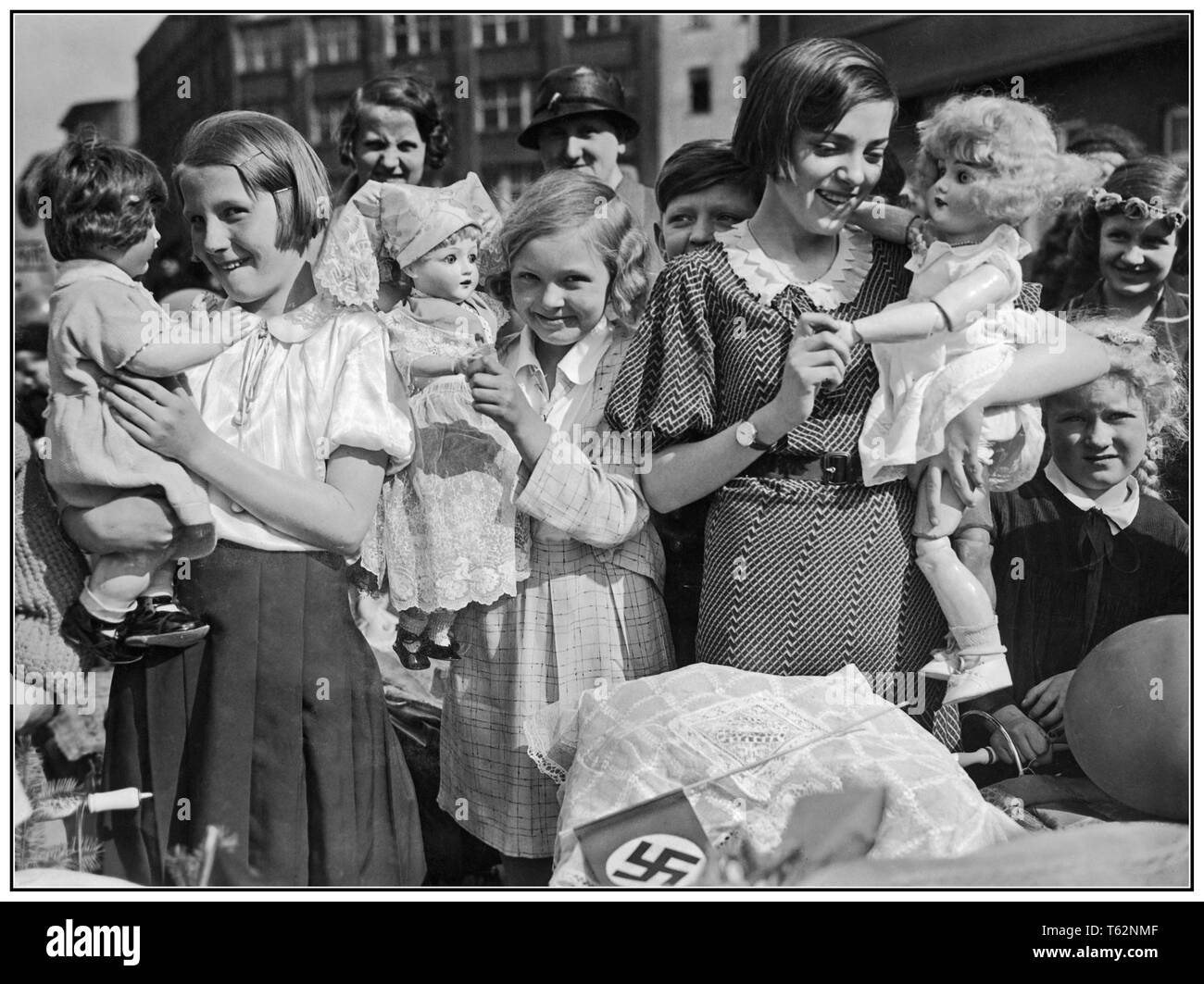 Vintage Nazi Propaganda image of a group of German girls with their dolls and prams, with swastika flag in foreground. They are preparing to go on a Mothers' and Children's day procession in Berlin Germany 1934 - Stock Image