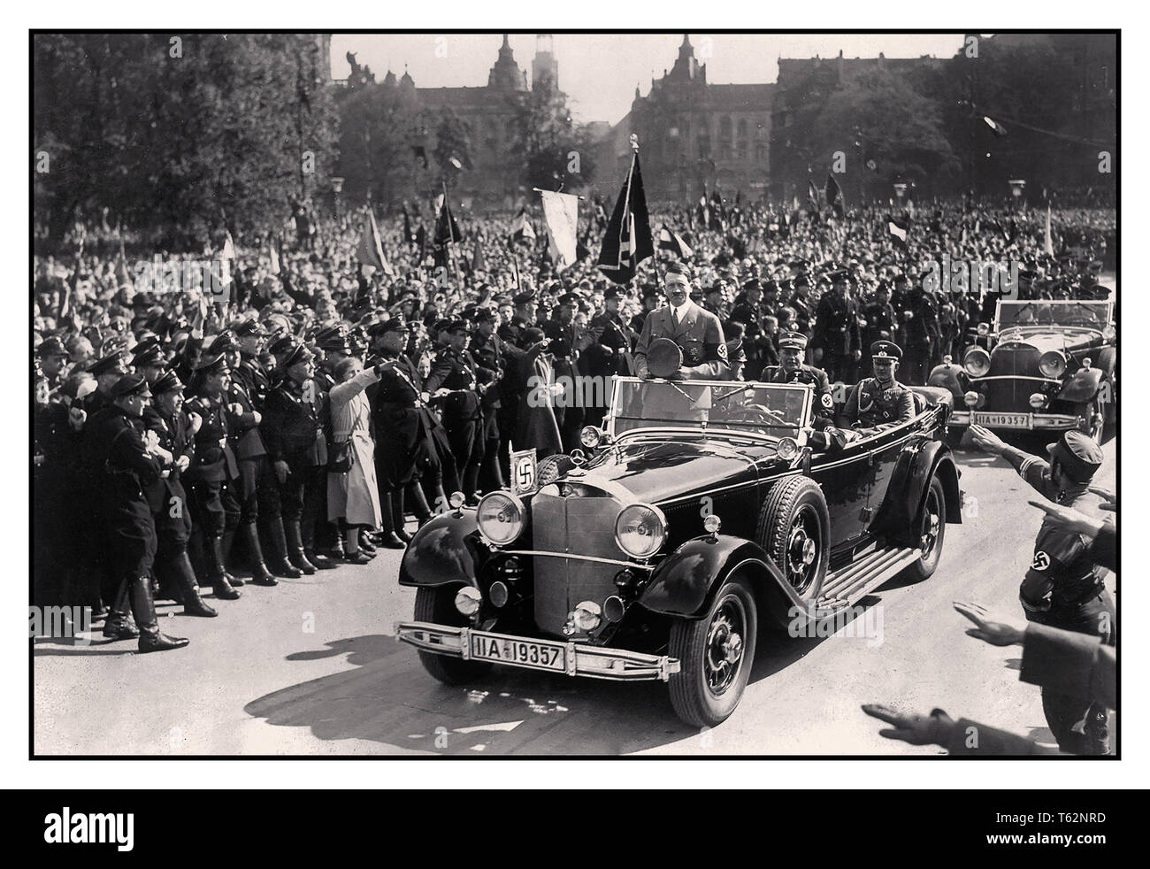 Adolf Hitler in Mercedes open car acknowledges the Nuremberg ecstatic crowds giving the Nazi Heil Hitler salute in his 1939 Mercedes-Benz 770K Gross Open Tourer motorcar which he used during Nazi parades - Stock Image
