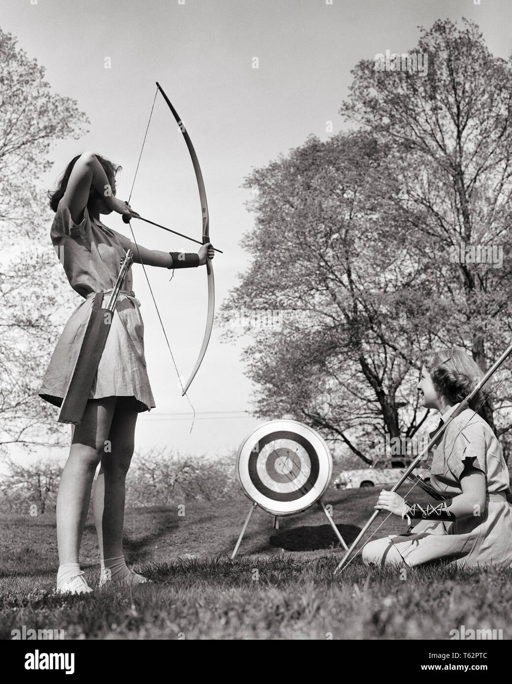 1950s TWO ANONYMOUS TEENAGE GIRLS PRACTICING ARCHERY TOGETHER AT CAMP IN COUNTRY - a1410 HAR001 HARS SAFETY COMPETITION ATHLETE RELAXING LIFESTYLE FEMALES RURAL COPY SPACE FRIENDSHIP FULL-LENGTH PHYSICAL FITNESS PERSONS ARCHERY RISK TEENAGE GIRL ARROW ATHLETIC CONFIDENCE B&W SUCCESS SKILL ACTIVITY AMUSEMENT HAPPINESS ARROWS HOBBY LEISURE STRENGTH INTEREST EXCITEMENT HOBBIES KNOWLEDGE RECREATION PASTIME ARCHER PLEASURE AT IN CONCEPTUAL BOWS STYLISH TEENAGED ANONYMOUS AIMING COACHING JUVENILES PRECISION RELAXATION TOGETHERNESS AMATEUR BLACK AND WHITE CAUCASIAN ETHNICITY ENJOYMENT HAR001 - Stock Image
