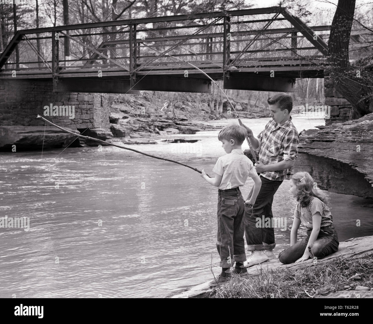 1950s YOUNG GIRL SITTING BESIDE CREEK BY ROAD BRIDGE WATCHING TWO BOYS FISHING IN RUSHING WATER USING LONG WOOD POLES AND STRING - a878 DEB001 HARS 1 JUVENILE BALANCE SAFETY ATHLETE LIFESTYLE FEMALES BROTHERS RURAL COPY SPACE FRIENDSHIP FULL-LENGTH STREAM MALES RISK ATHLETIC SIBLINGS CONFIDENCE SISTERS B&W POLES ADVENTURE RUSHING AND EXCITEMENT RECREATION BY IN SIBLING USING CONCEPTUAL BESIDE STICKS STYLISH DEB001 JUVENILES RELAXATION RODS TOGETHERNESS BLACK AND WHITE CAUCASIAN ETHNICITY CREEK OLD FASHIONED - Stock Image