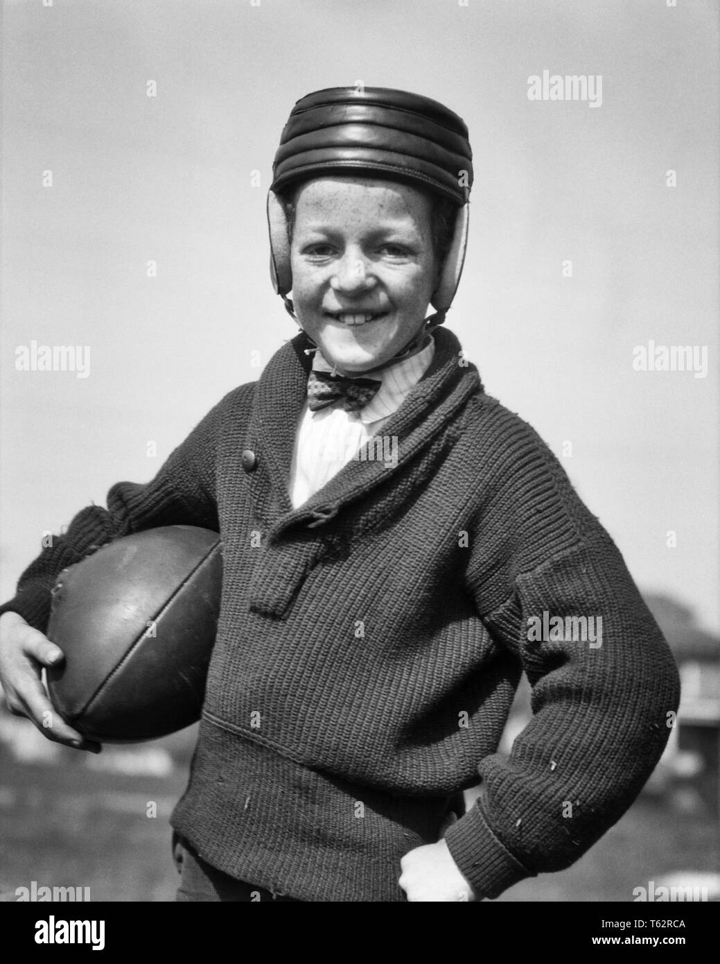 1920s SMILING FRECKLE FACE PRETEEN BOY WEARING EARLY LEATHER HELMET AND SHAWL-COLLAR SWEATER HOLDING FOOTBALL LOOKING AT CAMERA - b1806 HAR001 HARS FACIAL STYLE HEALTHY SAFETY LEADER COMPETITION ATHLETE RELAXING PLEASED JOY LIFESTYLE SATISFACTION CELEBRATION READY RURAL HEALTHINESS HOME LIFE ATHLETICS COPY SPACE HALF-LENGTH PHYSICAL FITNESS INSPIRATION MALES ATHLETIC ROUGH CONFIDENCE EXPRESSIONS B&W EYE CONTACT GOALS SUCCESS SKILL ACTIVITY AMUSEMENT HAPPINESS PHYSICAL CHEERFUL EARLY HOBBY PROTECTION STRENGTH STYLES VICTORY STRATEGY COURAGE INTEREST AND CHAMPION CHOICE EXCITEMENT HOBBIES - Stock Image
