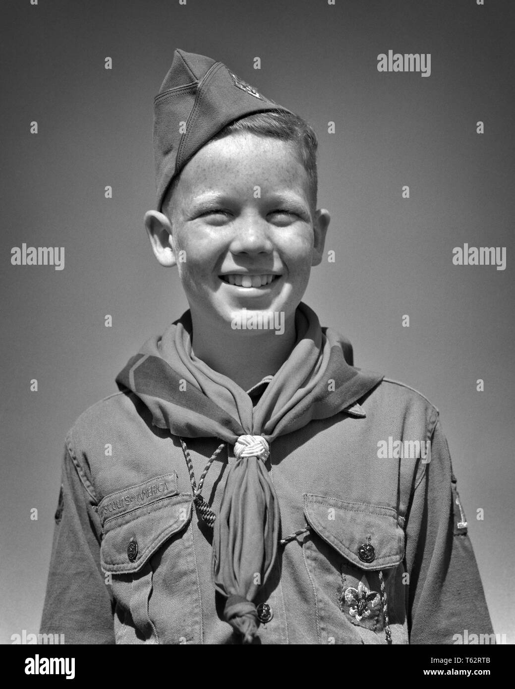 1950s SMILING PRETEEN BOY SCOUT IN UNIFORM CAP SHIRT NECKERCHIEF STANDING LOOKING AT CAMERA - b6115 HAR001 HARS HOME LIFE UNITED STATES HALF-LENGTH INSPIRATION SCOUTS UNITED STATES OF AMERICA MALES SPIRITUALITY CONFIDENCE EXPRESSIONS B&W EYE CONTACT FREEDOM HAPPINESS CHEERFUL ADVENTURE STRENGTH CHOICE EXCITEMENT KNOWLEDGE LEADERSHIP DIRECTION PRIDE NECKERCHIEF IN PRETEEN SMILES BOY SCOUT THRIFTY CONCEPTUAL COURTEOUS FRIENDLY HELPFUL JOYFUL KIND REVERENT STYLISH TRUSTWORTHY EAGER GROWTH JUVENILES LOYAL PRE-TEEN PRE-TEEN BOY BE PREPARED BLACK AND WHITE BRAVE CAUCASIAN ETHNICITY HAR001 OBEDIENT - Stock Image