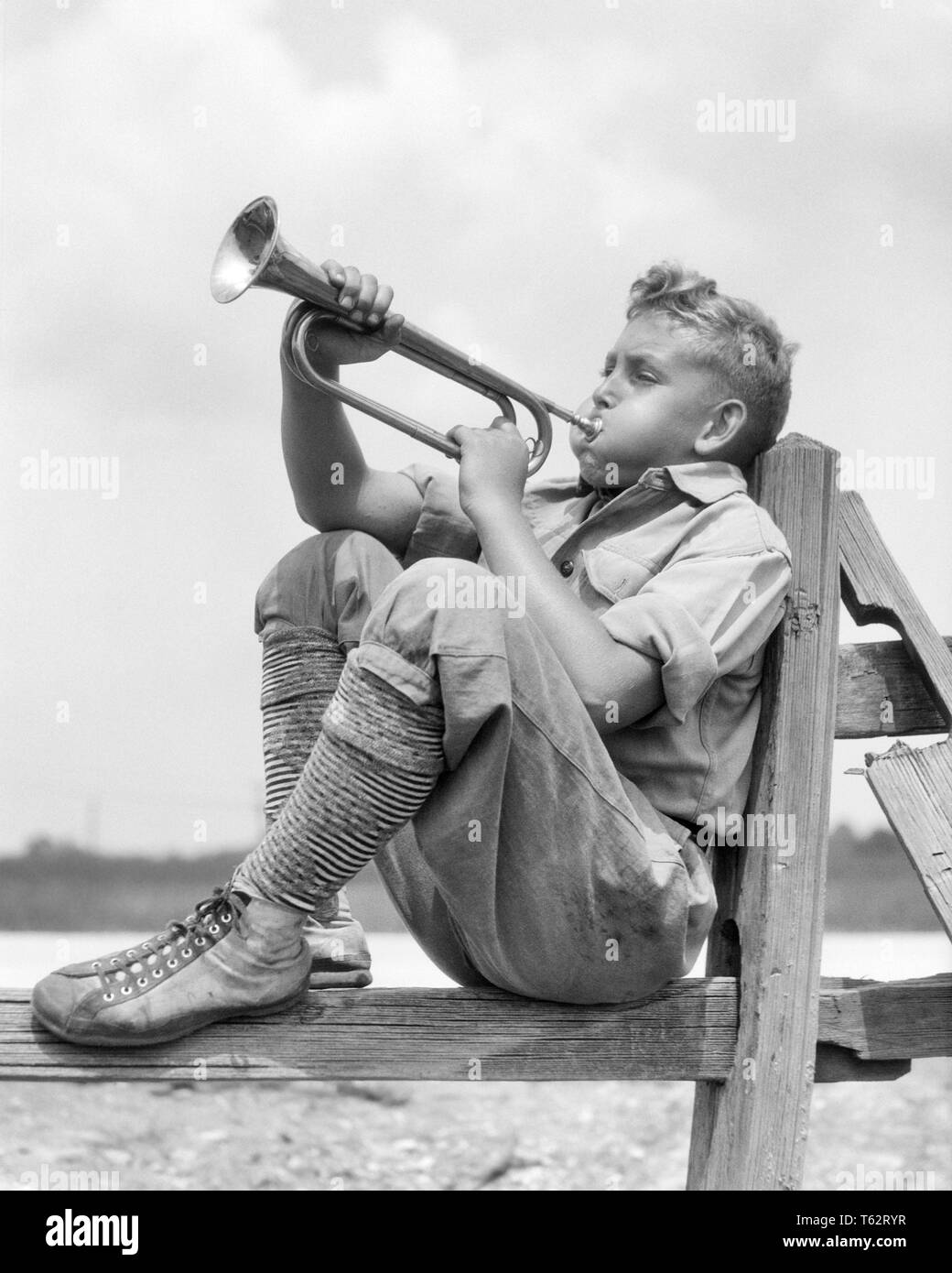 1930s PRETEEN BOY IN KNEE PANTS SOCKS AND SNEAKERS SITTING ON RAIL FENCE PLAYING BLOWING BUGLE - b7941 HAR001 HARS BRASS EXPRESSIONS B&W SUCCESS RAIL AND CHEEKS EXCITEMENT LOUD BULGING IN ON PRETEEN CONCEPTUAL BUGLE KNEE PANTS JUVENILES PRE-TEEN PRE-TEEN BOY BLACK AND WHITE CAUCASIAN ETHNICITY CONCENTRATING HAR001 OLD FASHIONED - Stock Image