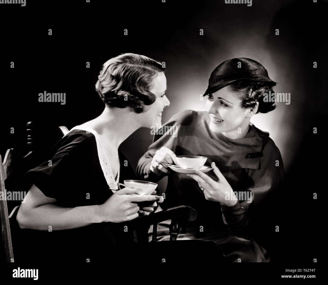 1930s TWO SMILING WOMEN SITTING TOGETHER DRINKING TEA TALKING AND GOSSIPING - bx002951 CAM001 HARS SIBLINGS SISTERS GOSSIPING B&W BEVERAGE DISCUSSING CAM001 SIBLING FRIENDLY STYLISH CUP AND SAUCER TEA CUP YOUNG ADULT WOMAN BLACK AND WHITE CAUCASIAN ETHNICITY OLD FASHIONED - Stock Image