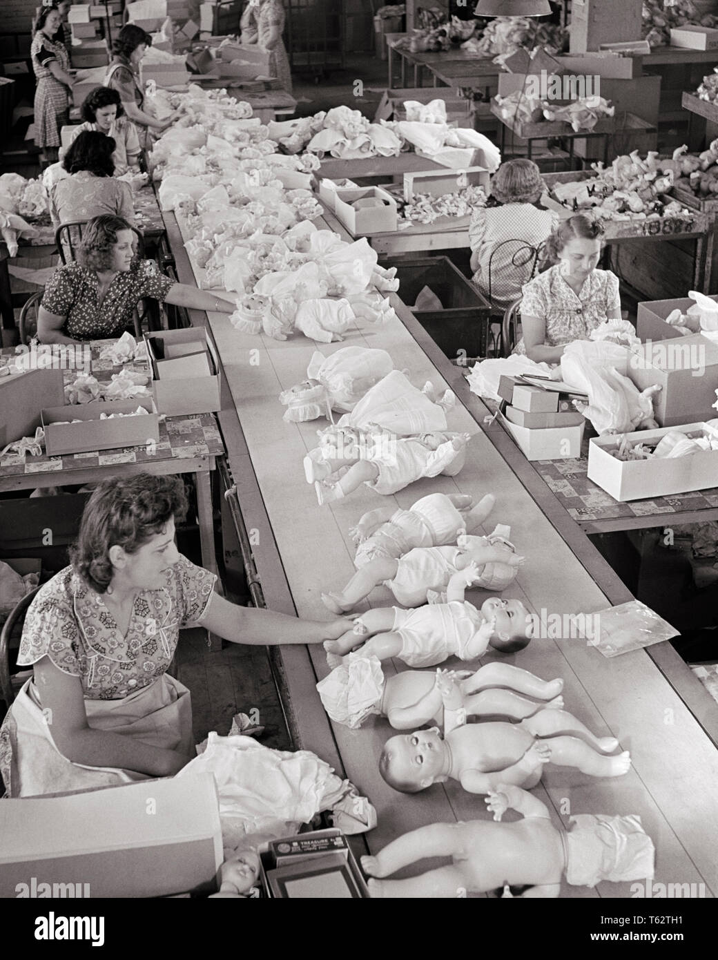 1950s women working on assembly line at doll factory dressing the dolls to putting in boxes