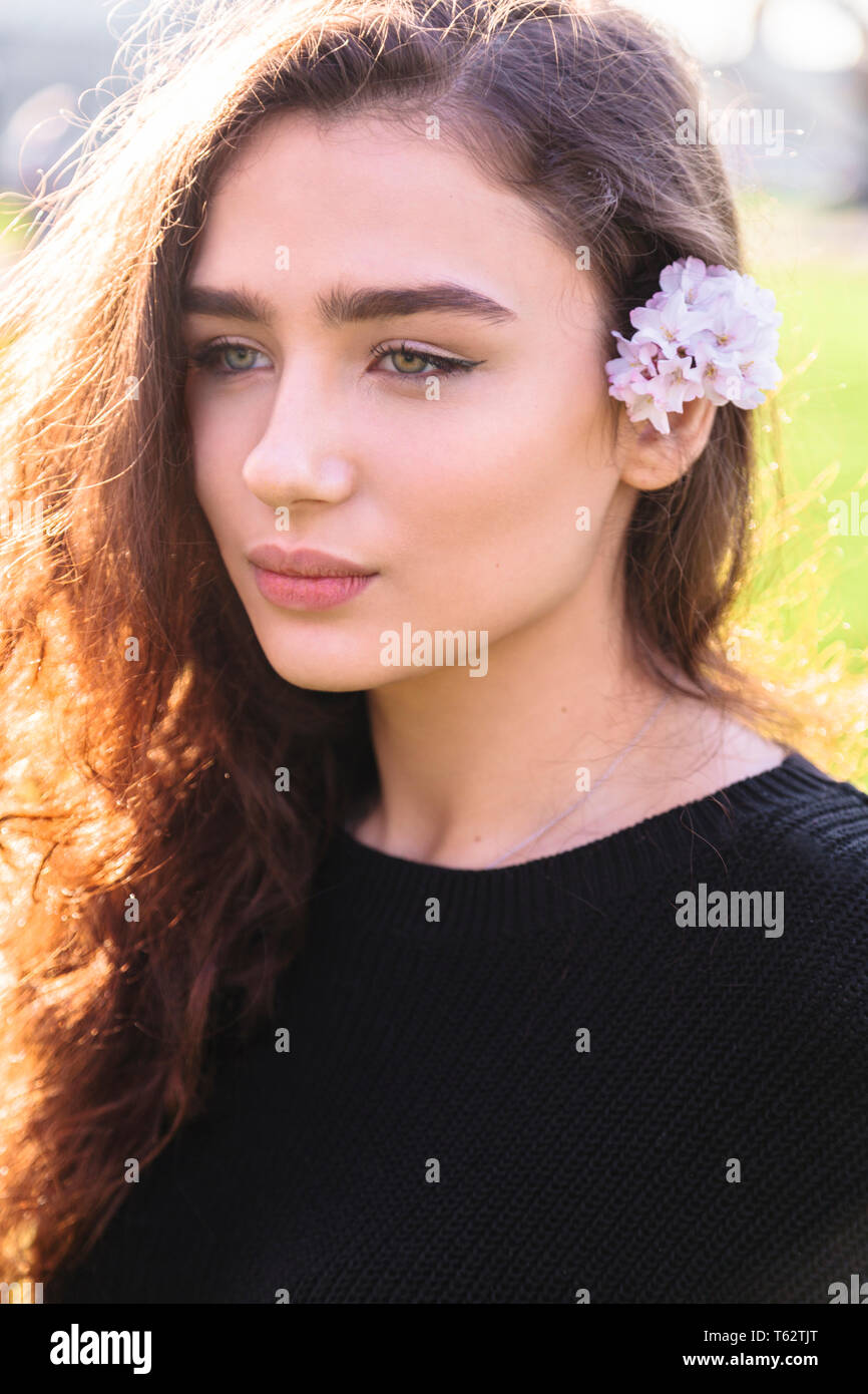 Portrait of woman with pink flower behind her ear - Stock Image
