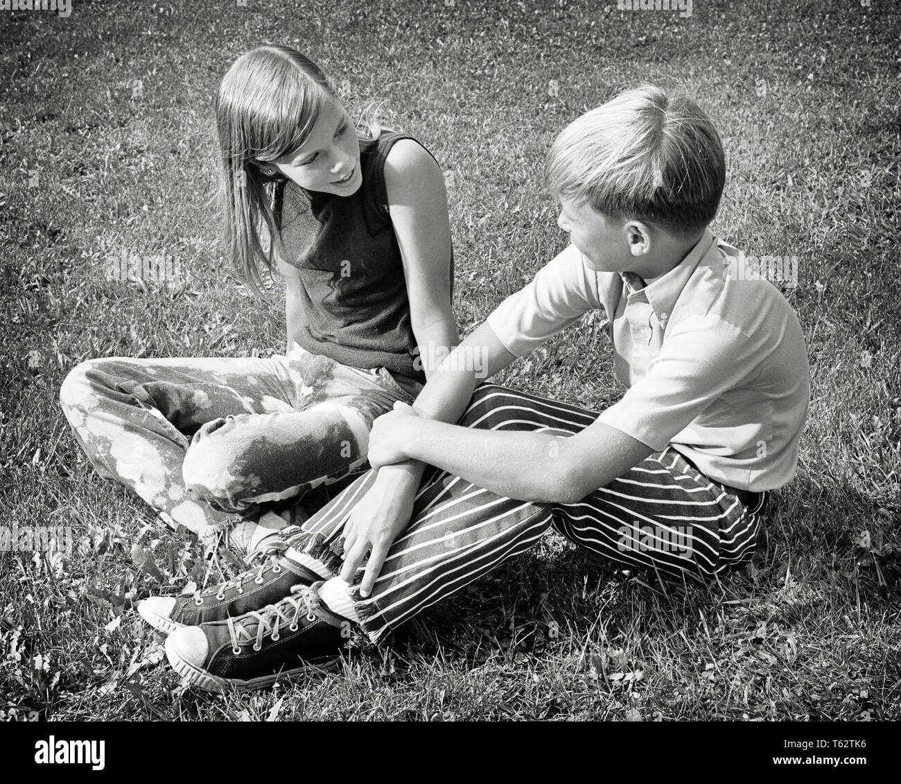 1970s BOY AND GIRL SITTING IN GRASS TALKING WEARING SUMMER CLOTHES SNEAKERS - j12933 HAR001 HARS FRIENDSHIP HALF-LENGTH BOYFRIEND MALES SNEAKERS SIBLINGS SISTERS B&W SUMMERTIME GIRLFRIEND HIGH ANGLE LEISURE AND TELLING SIBLING CONNECTION FRIENDLY STYLISH JUVENILES PRE-TEEN PRE-TEEN BOY PRE-TEEN GIRL TOGETHERNESS BLACK AND WHITE CAUCASIAN ETHNICITY HAR001 OLD FASHIONED - Stock Image