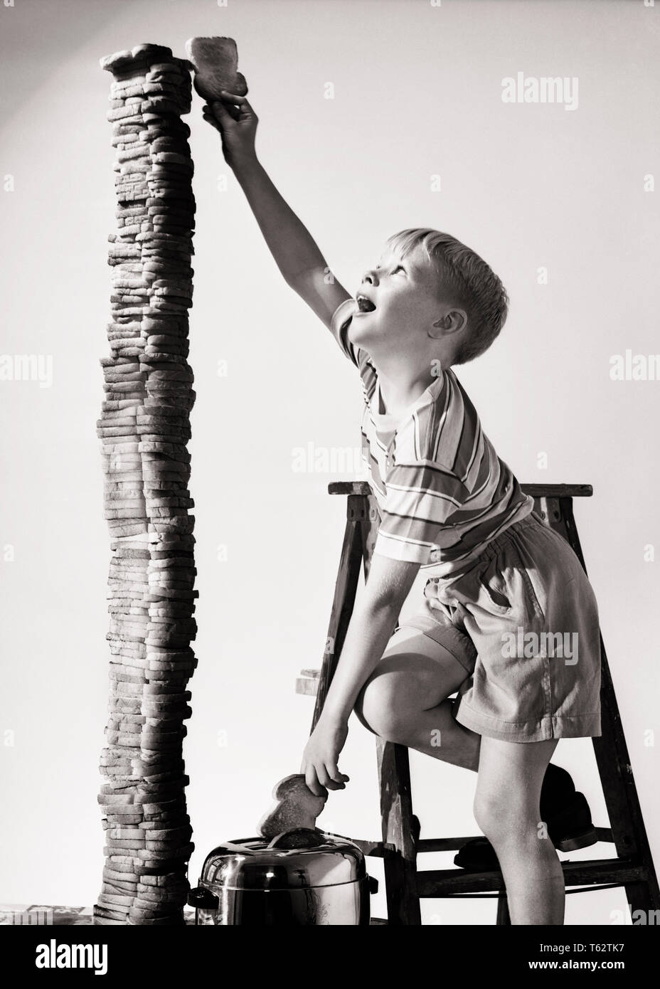 1950s EAGER BOY STANDING ON STEP LADDER REACHING THE TOP BUILDING A TOWER OF TOASTED BREAD SLICES - j15943 DEB001 HARS HALF-LENGTH MALES RISK PILES TROUBLED B&W BIZARRE TOWER HUNGRY PRANK HAPPINESS WEIRD ADVENTURE MISCHIEF TOAST STACKING CHALLENGE EXCITEMENT ZANY UNCONVENTIONAL MISCHIEVOUS TOWERING BAD BEHAVIOR CONCEPTUAL EXTREME IMAGINATION TOASTED WACKY DEB001 IDIOSYNCRATIC SHORT PANTS T-SHIRT MISCONDUCT AMUSING BEHAVIOR CREATIVITY EAGER ECCENTRIC JUVENILES PILING SKY HIGH TEE SHIRT BLACK AND WHITE CAUCASIAN ETHNICITY ERRATIC OLD FASHIONED OUTRAGEOUS TOWERS - Stock Image