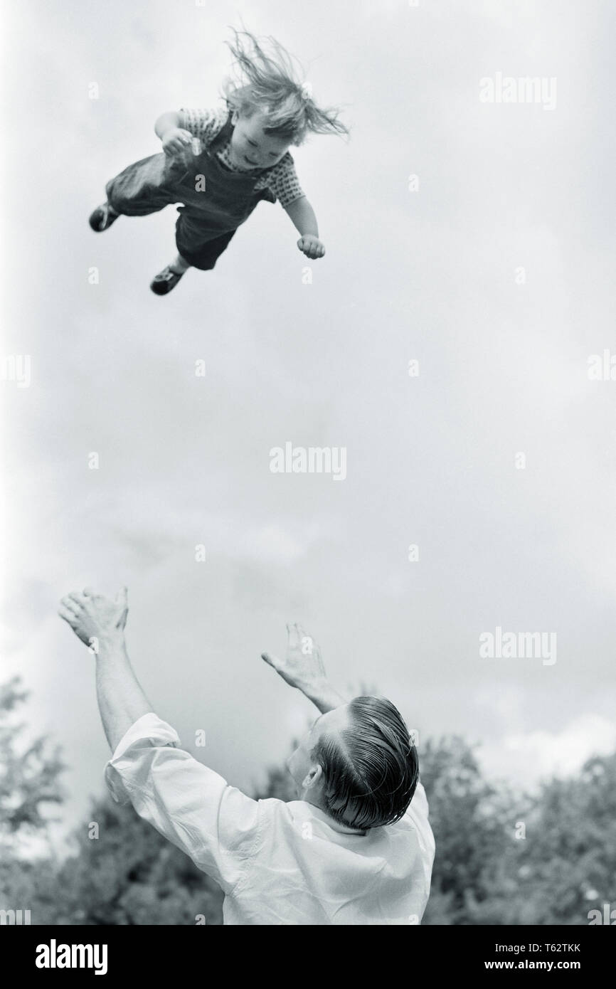1950s 1960s FUN OR DANGEROUSLY FOOLISH FATHER THROWING TODDLER DAUGHTER HIGH INTO THE AIR AND WAITING TO CATCH HER COMING DOWN - j1789 LAN001 HARS THROWING SAFETY JOY LIFESTYLE FEMALES RURAL HOME LIFE COPY SPACE CATCH FULL-LENGTH PHYSICAL FITNESS DAUGHTERS PERSONS CARING DANGER MALES RISK CONFIDENCE FATHERS B&W FREEDOM HAPPINESS HEAD AND SHOULDERS HIGH ANGLE PROTECTION STRENGTH AND DADS EXCITEMENT LOW ANGLE FOOLISH INTO THE TO AUTHORITY CONCEPTUAL TOSSING OR GROWTH JUVENILES MID-ADULT MID-ADULT MAN RELAXATION TOGETHERNESS BABY GIRL BLACK AND WHITE CAUCASIAN ETHNICITY OLD FASHIONED - Stock Image