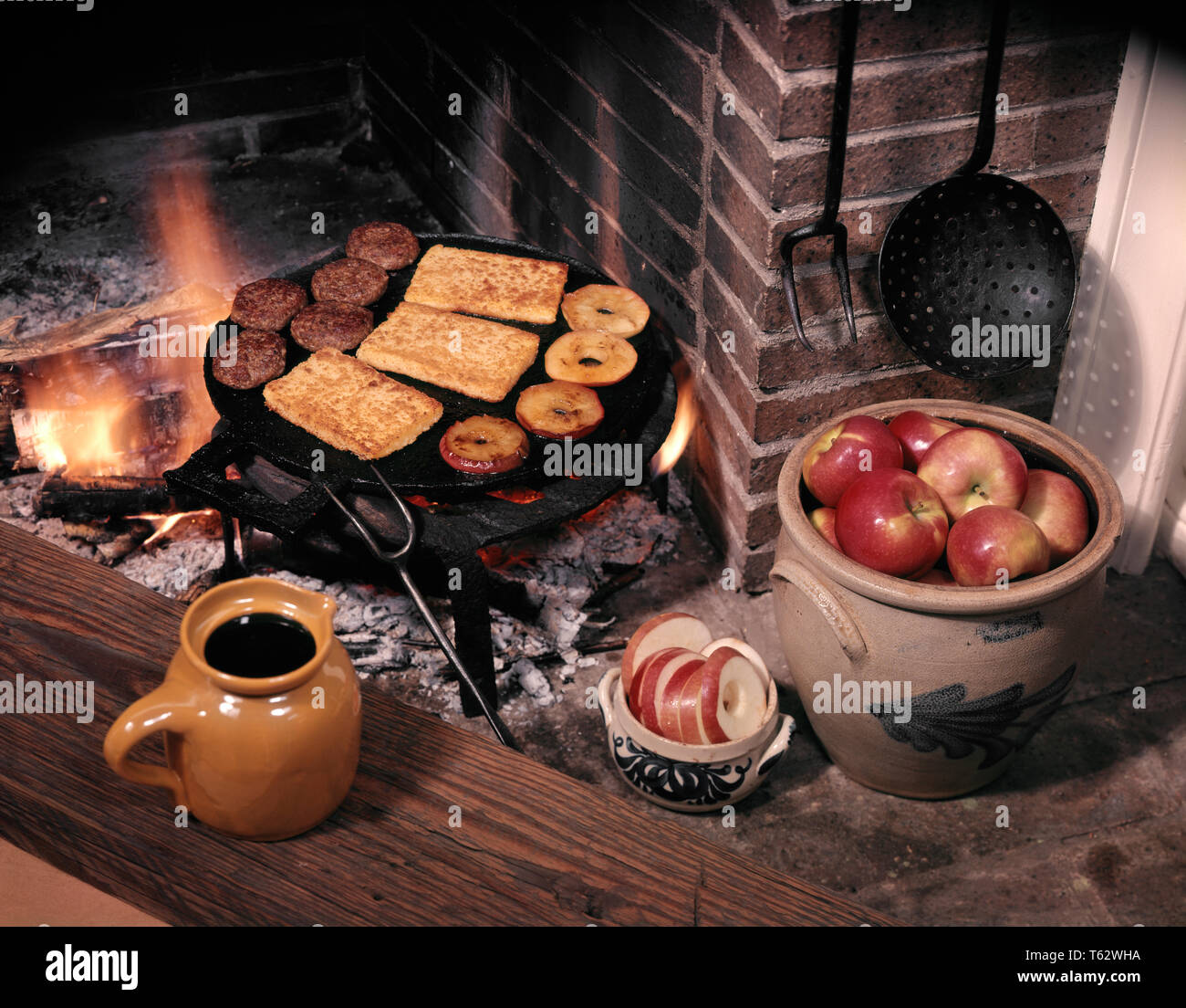 1970s 1770s COLONIAL AMERICAN BREAKFAST MEAL HASTY PUDDING CORN MUSH BEING FRIED WITH APPLE RINGS SAUSAGE ON FIREPLACE GRILL - kf38885 FRT001 HARS EARLY KNOWLEDGE LADLE ON 1776 PORK WAR OF INDEPENDENCE CONCEPTUAL STILL LIFE STYLISH REVOLT AMERICAN REVOLUTIONARY WAR 1770s COLONIES PRIMITIVE PUDDING SAUSAGE OLD FASHIONED YANKEE DOODLE - Stock Image