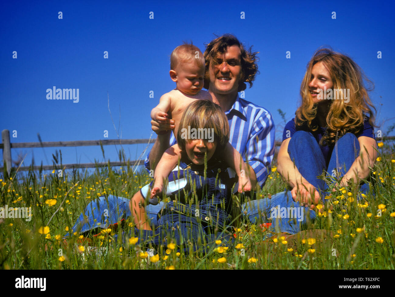 1970s SMILING HAPPY HIPPIE FAMILY OF FOUR FATHER MOTHER TODDLER AND BABY SONS SITTING TOGETHER IN SPRING FIELD OF WILDFLOWERS - kj6287 HAR001 HARS HUSBAND DAD FOUR MOM CLOTHING FACES NOSTALGIC PAIR ROMANCE 4 BEAUTY SPRING COLOR MOTHERS EXPRESSION OLD TIME HIPPIE NOSTALGIA BROTHER OLD FASHION 1 JUVENILE FACIAL STYLE TEAMWORK SONS PLEASED FAMILIES JOY LIFESTYLE FEMALES MARRIED BROTHERS RURAL SPOUSE HUSBANDS HEALTHINESS NATURE COPY SPACE FULL-LENGTH LADIES PERSONS SCENIC CARING MALES SIBLINGS SPIRITUALITY CONFIDENCE EXPRESSIONS FATHERS PARTNER FREEDOM WIDE ANGLE HAPPINESS CHEERFUL ADVENTURE - Stock Image
