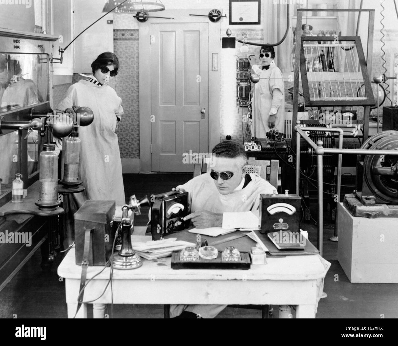 1920s THREE MAD SCIENTISTS WORKING EXPERIMENTING INVENTING IN ELECTRONICS LABORATORY ALL WEARING DARK GOGGLES & WHITE LAB COATS - kl800280 CAM001 HARS COATS LABORATORY HORIZONTAL COPY SPACE FULL-LENGTH HALF-LENGTH LADIES PERSONS INSPIRATION GOGGLES MALES RISK SCIENTISTS B&W BIZARRE TEMPTATION WEIRD HIGH ANGLE DISCOVERY STRENGTH ELECTRONICS EXCITEMENT POWERFUL CAM001 ZANY UNCONVENTIONAL IN OCCUPATIONS HIGH TECH CONCEPTUAL INVENTION STYLISH IDIOSYNCRATIC SCI-FI AMUSING ECCENTRIC IDEAS INVENTING MID-ADULT MID-ADULT MAN MID-ADULT WOMAN SCIENCE FICTION TOGETHERNESS & BLACK AND WHITE - Stock Image