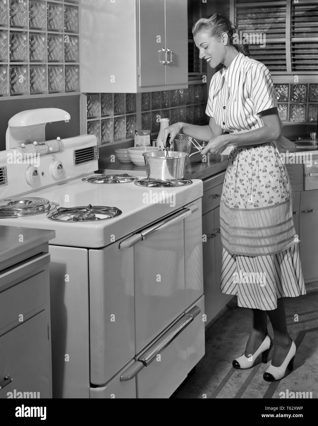 1950s SMILING BLOND HOUSEWIFE WEARING DRESS APRON TWO TONE HIGH HEEL SHOES COOKING ON MID-CENTURY MODERN ELECTRIC KITCHEN RANGE - kr001040 CAM001 HARS JOY LIFESTYLE SATISFACTION FEMALES HOME LIFE LUXURY COPY SPACE FULL-LENGTH LADIES PERSONS INSPIRATION B&W HOMEMAKER HAPPINESS HOMEMAKERS CHEERFUL HIGH HEEL CAM001 PRIDE ON HOUSEWIVES SMILES CONCEPTUAL JOYFUL RANGE STYLISH ALUMINUM GLASS BLOCK TWO TONE YOUNG ADULT WOMAN BLACK AND WHITE CAUCASIAN ETHNICITY OLD FASHIONED - Stock Image