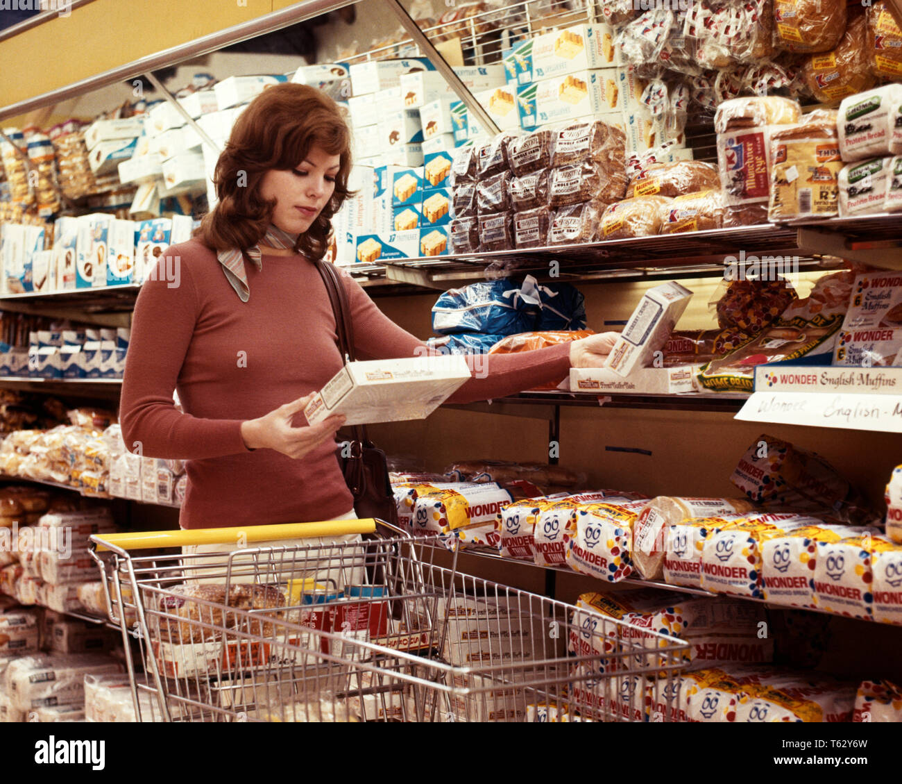 1970s YOUNG WOMAN HOUSEWIFE FOOD SHOPPING COMPARING TWO ITEMS GROCERY STORE BAKERY DEPARTMENT CART - ks14455 KRU001 HARS GROWNUP HEALTHINESS HOME LIFE HALF-LENGTH LADIES PERSONS GROWN-UP SHOPPER BRUNETTE HOMEMAKER WONDER HOMEMAKERS ITEMS CUSTOMER SERVICE CHOICE HOUSEWIVES SELECTION CONCEPTUAL BAKERY DECIDING NOURISHMENT STYLISH COMPARE YOUNG ADULT WOMAN YOUNGSTER CAUCASIAN ETHNICITY COMPARING OLD FASHIONED SELECTING - Stock Image