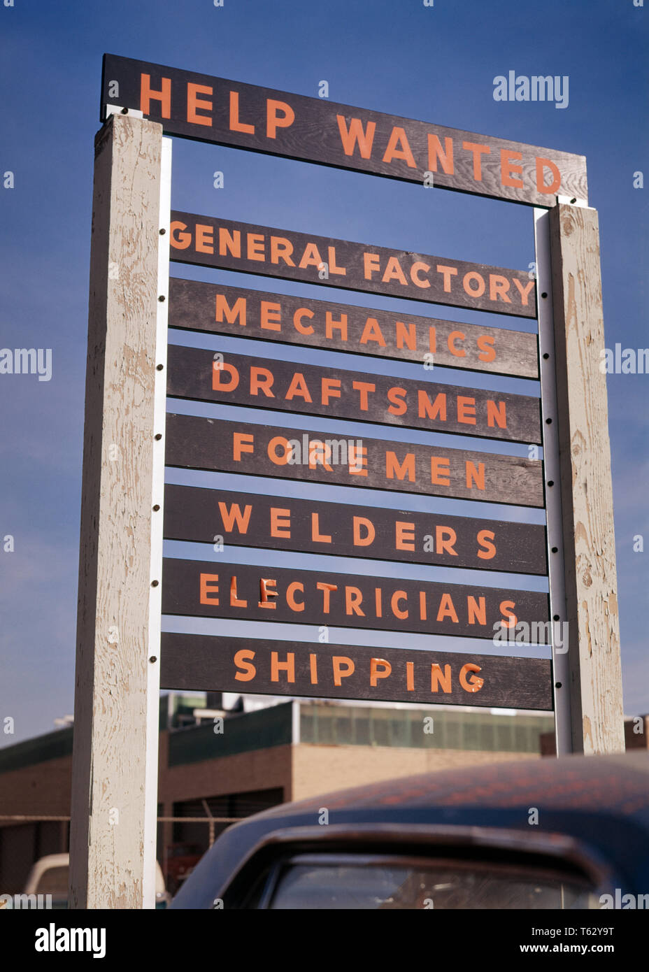 1960s HELP WANTED SIGN OUTSIDE FACTORY FOR ALL BLUE COLLAR JOBS MECHANICS DRAFTSMEN WELDERS ELECTRICIANS SHIPPING AND FOREMEN - ks4216 HAR001 HARS DRAFTSMEN HELP WANTED NEED PRECISION SHIPPING WANTED FACTORIES HAR001 OLD FASHIONED - Stock Image