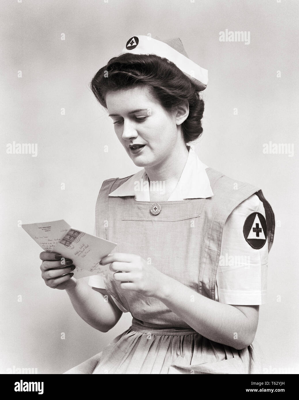 6be1a848141 1940s WOMAN SERVING VOLUNTEER RED CROSS NURSE WEARING UNIFORM SMOCK DRESS  AND CAP READING LETTER DURING