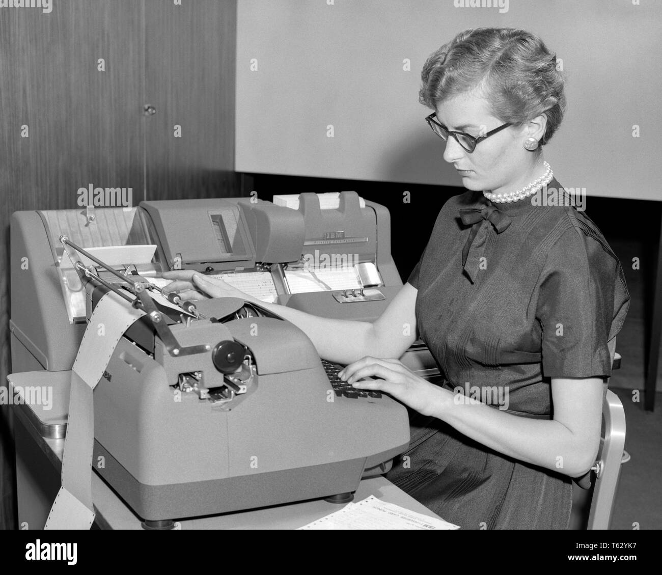 1950s WOMAN AT ELECTRIC TYPEWRITER CREATING DATA PROCESSING CARDS FOR IBM CARDATYPE ACCOUNTING SYSTEM - o1221 HAR001 HARS EYEGLASSES B&W DATA PROCESSING SKILL OCCUPATION SKILLS PROGRESS INNOVATION LABOR CREATING EMPLOYMENT OCCUPATIONS DATA ENTRY ACCOUNTING SECRETARIES EMPLOYEE ENTRY KEY PUNCH MID-ADULT MID-ADULT WOMAN BLACK AND WHITE CAUCASIAN ETHNICITY CLERICAL HAR001 LABORING OLD FASHIONED - Stock Image