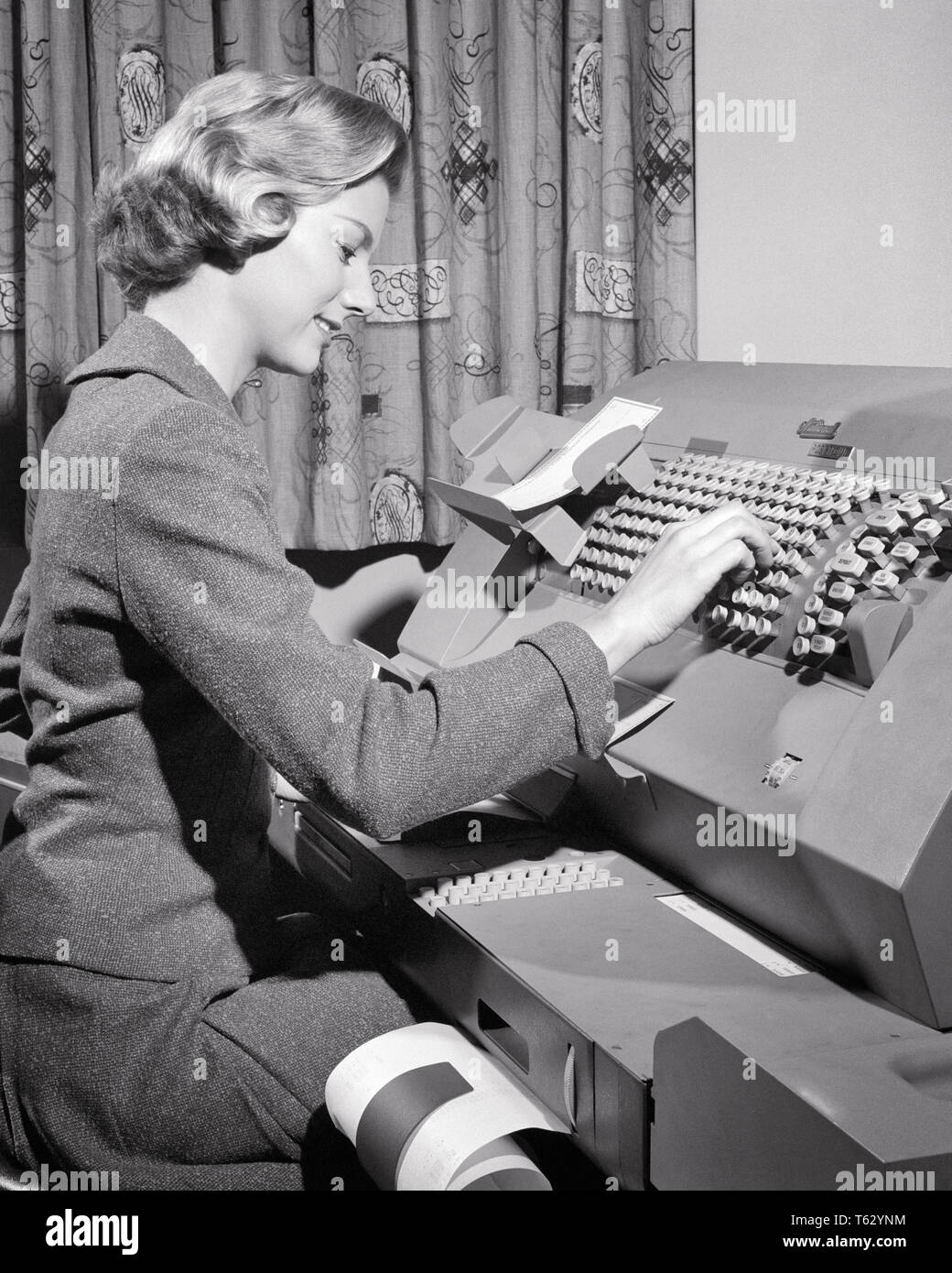 1950s WOMAN WORKING AT DATA PROCESSING CARDATYPE MACHINE - o402 HAR001 HARS B&W DATA PROCESSING SKILL OCCUPATION SKILLS ELECTRONICS PROGRESS INNOVATION LABOR CREATING EMPLOYMENT OCCUPATIONS DATA ENTRY ACCOUNTING SECRETARIES EMPLOYEE ENTRY KEY PUNCH MID-ADULT MID-ADULT WOMAN YOUNG ADULT WOMAN BLACK AND WHITE CAUCASIAN ETHNICITY CLERICAL HAR001 LABORING OLD FASHIONED - Stock Image