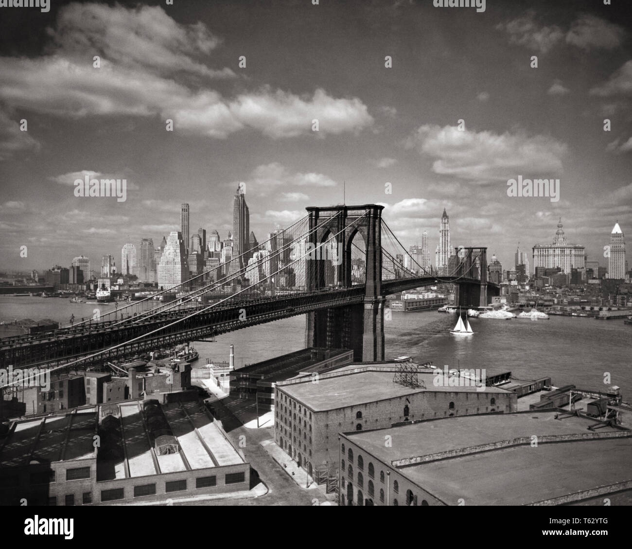 1930s NEW YORK CITY BROOKLYN BRIDGE AND THE SKYLINE OF LOWER MANHATTAN ACROSS THE EAST RIVER - q36336 CPC001 HARS BLACK AND WHITE BRIDGES BROOKLYN BRIDGE EAST RIVER FINANCIAL DISTRICT LOWER MANHATTAN OLD FASHIONED SKYSCRAPERS SUSPENSION - Stock Image