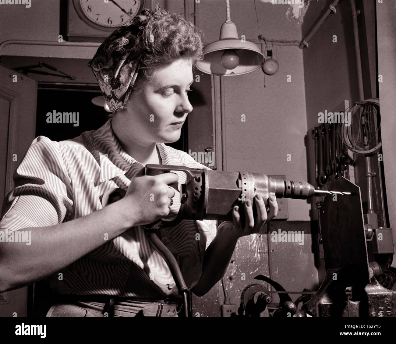 1940s PATRIOTIC ANONYMOUS UNIDENTIFIED WOMAN HOME FRONT INDUSTRIAL WORKER USING ELECTRICAL HAND DRILL DURING WORLD WAR II - q43367 CPC001 HARS FEMALES WW2 JOBS HALF-LENGTH LADIES PERSONS INSPIRATION CONFIDENCE B&W GOALS SUCCESS SKILL OCCUPATION SKILLS HOME FRONT STRENGTH VICTORY COURAGE CHOICE KNOWLEDGE LOW ANGLE POWERFUL WORLD WARS LABOR PRIDE WORLD WAR WORLD WAR TWO WORLD WAR II AUTHORITY EMPLOYMENT OCCUPATIONS UNIDENTIFIED USING CONCEPTUAL PATRIOTIC ROSIE THE RIVETER STYLISH WORLD WAR 2 ANONYMOUS EMPLOYEE PRECISION YOUNG ADULT WOMAN BLACK AND WHITE CAUCASIAN ETHNICITY DURING LABORING - Stock Image