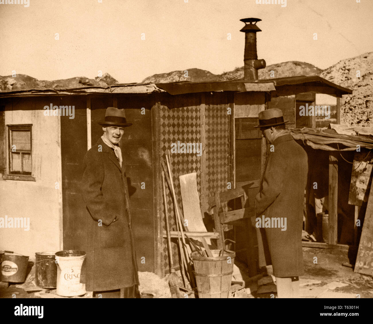 1930s TWO MEN IN HATS AND OVERCOATS STANDING BY HOOVERVILLE SHANTY TOWN TRAILER PARK DEPRESSION VILLAGE VARIOUS CITIES USA - q73981 CPC001 HARS COPY SPACE FULL-LENGTH PERSONS VILLAGE UNITED STATES OF AMERICA MALES RISK ROUGH EXPRESSIONS B&W SADNESS SHELTER DISASTER HOMELESS STRENGTH STRATEGY AND EXTERIOR POWERFUL PROGRESS CONDITIONS BY IN POLITICS OVERCOATS CONCEPTUAL CITIES TEMPORARY VARIOUS ANONYMOUS BUILT COOPERATION MID-ADULT MID-ADULT MAN SHANTY TOGETHERNESS BLACK AND WHITE CAUCASIAN ETHNICITY DEFEATED DURING GREAT DEPRESSION HOOVERVILLE OLD FASHIONED SHANTY TOWN - Stock Image