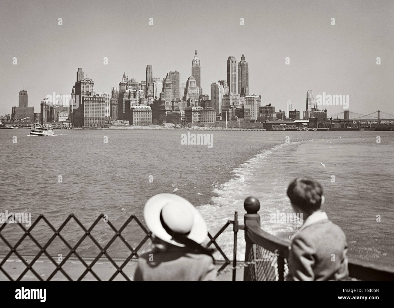 1950s YOUNG GIRL AND BOY RIDING ON STATEN ISLAND FERRY BOAT VIEWING SKYLINE OF LOWER MANHATTAN AND NEW YORK HARBOR NYC USA - r1649 HAR001 HARS HISTORY CELEBRATION FEMALES BROTHERS UNITED STATES COPY SPACE HALF-LENGTH LOWER SCENIC INSPIRATION UNITED STATES OF AMERICA MALES SIBLINGS CONFIDENCE SISTERS TRANSPORTATION B&W HARBOR FREEDOM WIDE ANGLE VISION DREAMS HEAD AND SHOULDERS ADVENTURE STRENGTH AND EXCITEMENT EXTERIOR LOOKING BACK OF ON NYC SIBLING CONCEPTUAL NEW YORK CITIES FERRY IMAGINATION STYLISH NEW YORK CITY JUVENILES TOGETHERNESS VIEWING BLACK AND WHITE CAUCASIAN ETHNICITY HAR001 - Stock Image