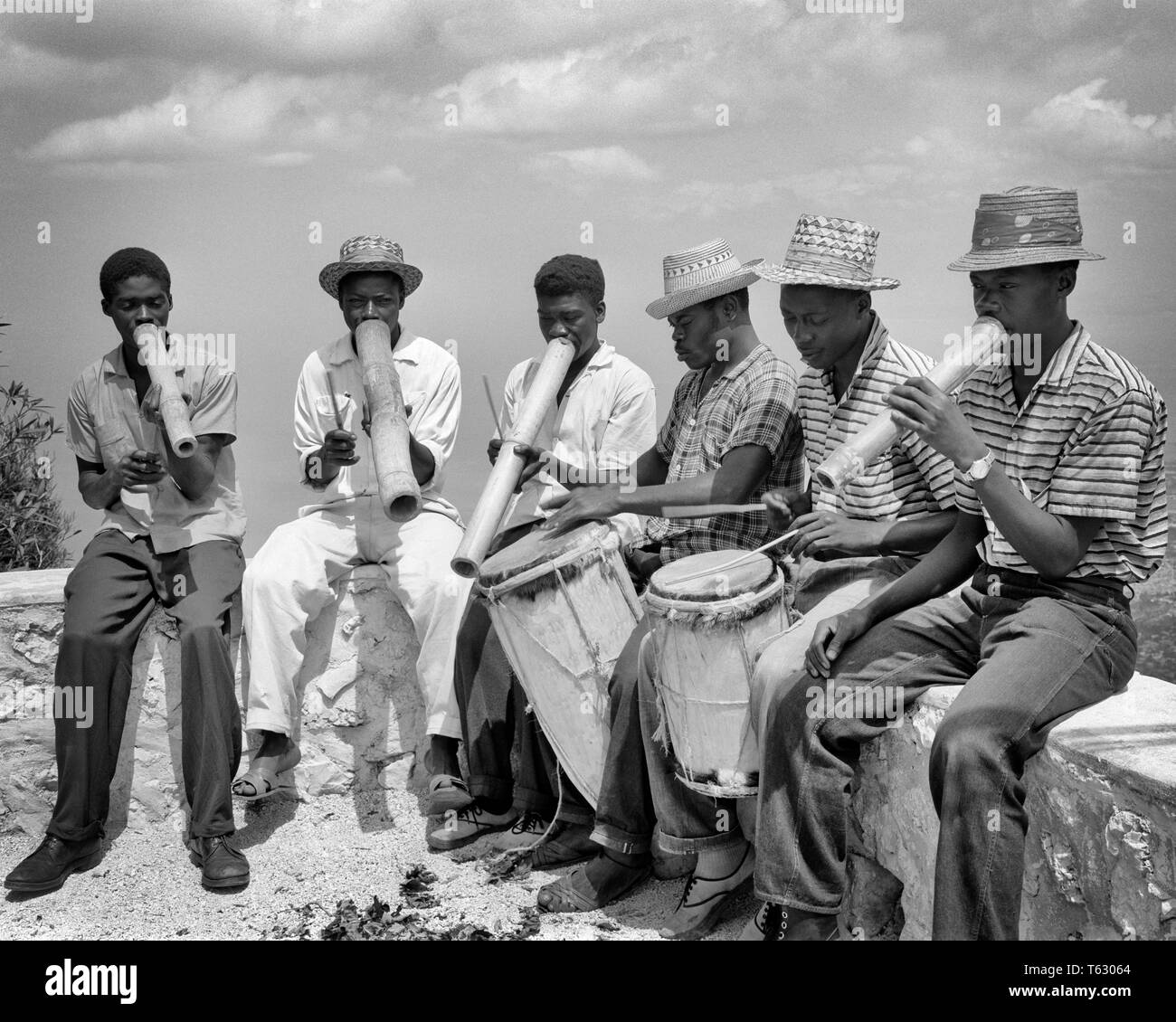1960s BAND OF ANONYMOUS NATIVE HAITIAN MUSICIANS PLAYING HAND MADE INSTRUMENTS SITTING ON WALL OUTDOOR  - r17196 LAN001 HARS 6 COMMUNICATING DRUMS PERSONS MALES CARIBBEAN SIX PROFESSION ENTERTAINMENT B&W HORNS MUSICIANS SKILL MINORITY OCCUPATION SKILLS PERCUSSION INSTRUMENT MANUAL PERFORMER PERCUSSION CAREERS ETHNIC DIVERSITY OF ON ENTERTAINER OCCUPATIONS MUSICAL INSTRUMENT ORCHESTRAS BLACKS MUSICAL INSTRUMENTS PERCUSSION INSTRUMENTS ANONYMOUS MUSICAL EQUIPMENT COMMUNICATE ENTERTAINERS HAITIAN MINORITIES PERFORMERS BLACK AND WHITE HISPANIOLA OLD FASHIONED WIND INSTRUMENT WIND INSTRUMENTS - Stock Image