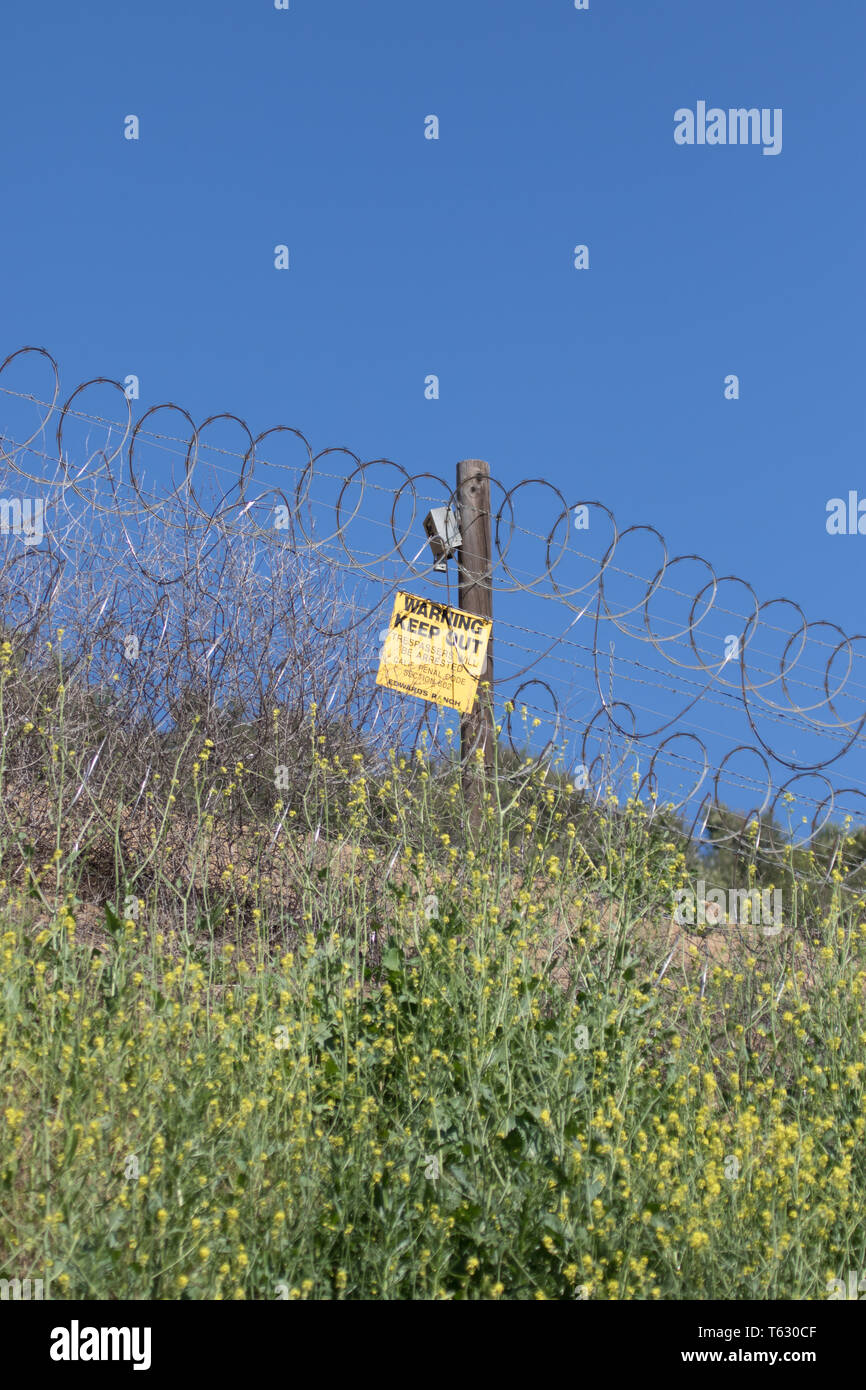 Warning keep out sign and barbed wire fence  attached to a wooden post marking a private property boundary in a rural area - Stock Image