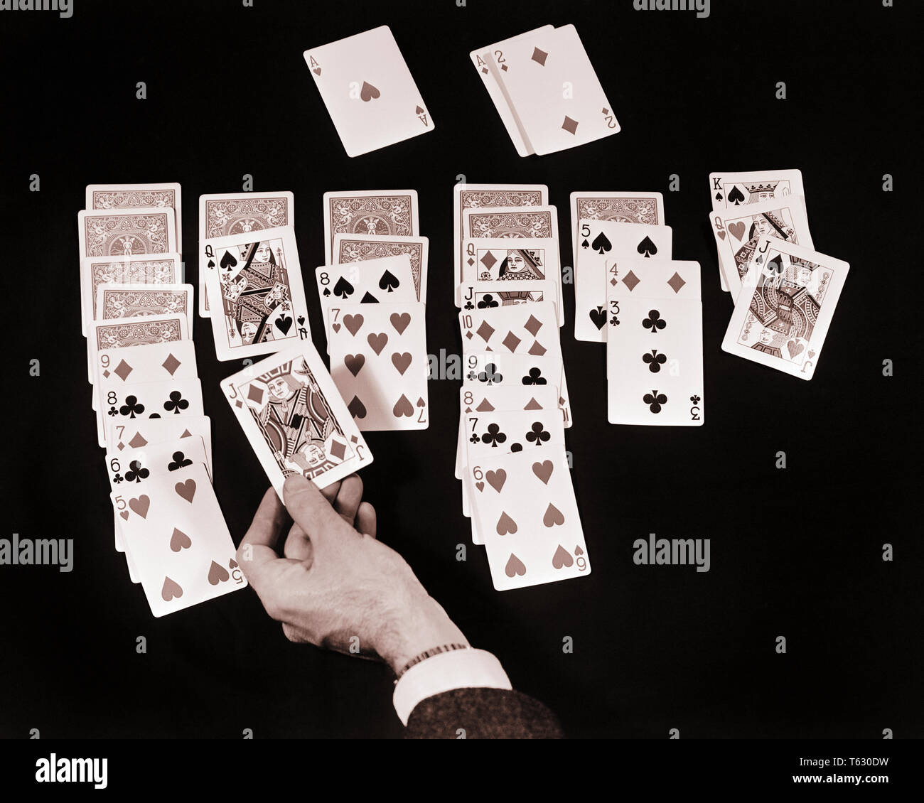 1930s SYMBOLIC SOLITAIRE TABLETOP CARD GAME MALE HAND PLACING RED JACK OF DIAMONDS ON BLACK QUEEN OF SPADES - s12574 HAR001 HARS RECREATION TABLETOP ON CONCEPT CONCEPTUAL CLOSE-UP SOLITAIRE SYMBOLIC CONCEPTS RELAXATION WASTE OF TIME BLACK AND WHITE CAUCASIAN ETHNICITY CONCENTRATION DIVERSION HANDS ONLY HAR001 OLD FASHIONED PLACING REPRESENTATION - Stock Image