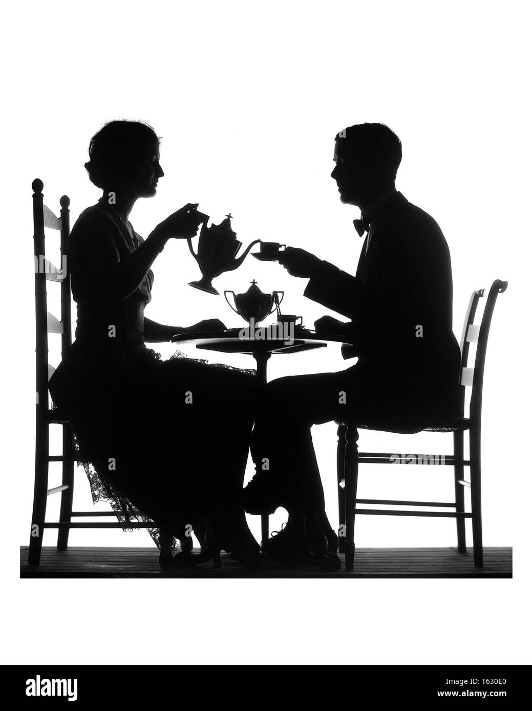 1920s SILHOUETTE ANONYMOUS MAN AND WOMAN AT TEA WOMAN POURING MAN HOLDING CUP AND SAUCER BOTH SITTING IN CHAIRS AT SMALL TABLE - s1290 HAR001 HARS HUSBANDS HOME LIFE LUXURY COPY SPACE FRIENDSHIP FULL-LENGTH LADIES PERSONS MALES SILHOUETTES B&W OUTLINE PARTNER DATING BEVERAGE SILHOUETTED AND ATTRACTION CONNECTION COURTSHIP CONCEPTUAL STILL LIFE STYLISH MAN'S ANONYMOUS POSSIBILITY COOPERATION MID-ADULT MID-ADULT MAN MID-ADULT WOMAN SOCIAL ACTIVITY TOGETHERNESS WIVES AFTERNOON BLACK AND WHITE COURTING HAR001 OLD FASHIONED TEA FOR TWO Stock Photo
