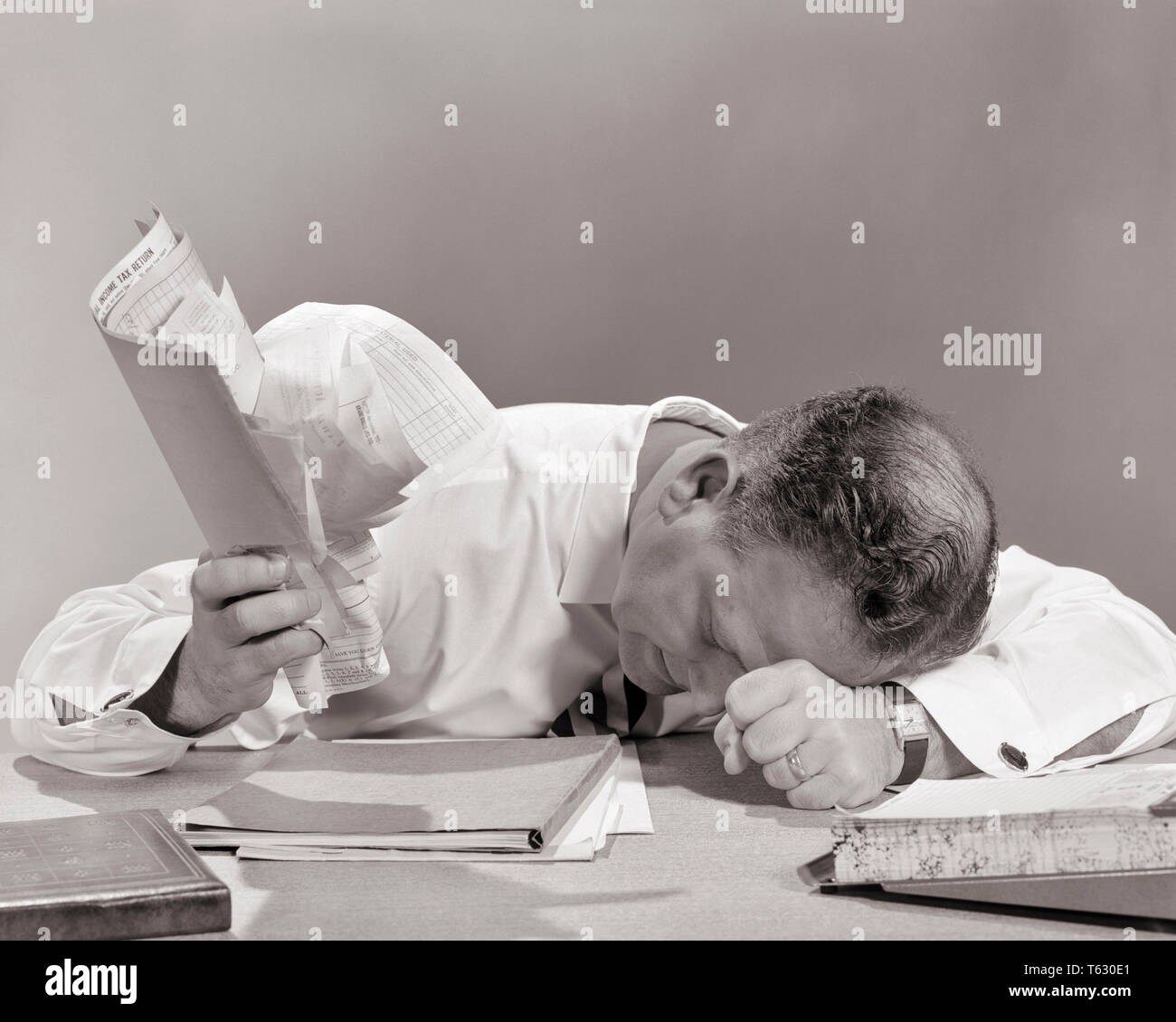 1950s EXASPERATED businessman at desk head down resting on fist holding BILLS INVOICES documents papers clutched in other hand - s12996 HAR001 HARS ANGER FEAR COMMUNICATION FIST COMPETITION INFORMATION LIFESTYLE JOBS STUDIO SHOT MOODY MANAGER COPY SPACE PERSONS MALES RISK EXECUTIVES HEADACHE EXPRESSIONS TROUBLED B&W RESTING SADNESS WHITE COLLAR SKILL OCCUPATION DOCUMENTS SKILLS HEAD AND SHOULDERS HIGH ANGLE OVERWHELMED BALDING KNOWLEDGE BAD NEWS BANKRUPTCY AT IN OF ON EMPLOYMENT FRUSTRATION MOOD OCCUPATIONS BOSSES CONCEPTUAL GLUM ESCAPE BALD SPOT BANKRUPT EMPLOYEE PAPER WORK DISGRUNTLED - Stock Image