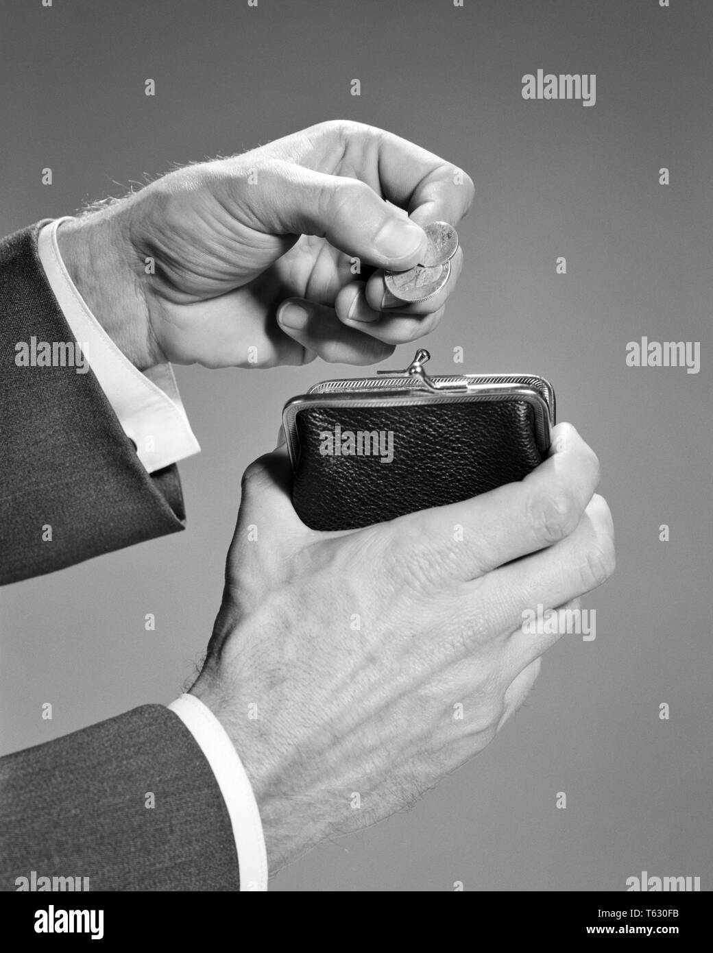 1960s MALE HANDS DROPPING COINS QUARTER AND DIME INTO A CHANGE PURSE - s13875 HAR001 HARS MID-ADULT MID-ADULT MAN BLACK AND WHITE CAUCASIAN ETHNICITY HANDS ONLY HAR001 OLD FASHIONED - Stock Image
