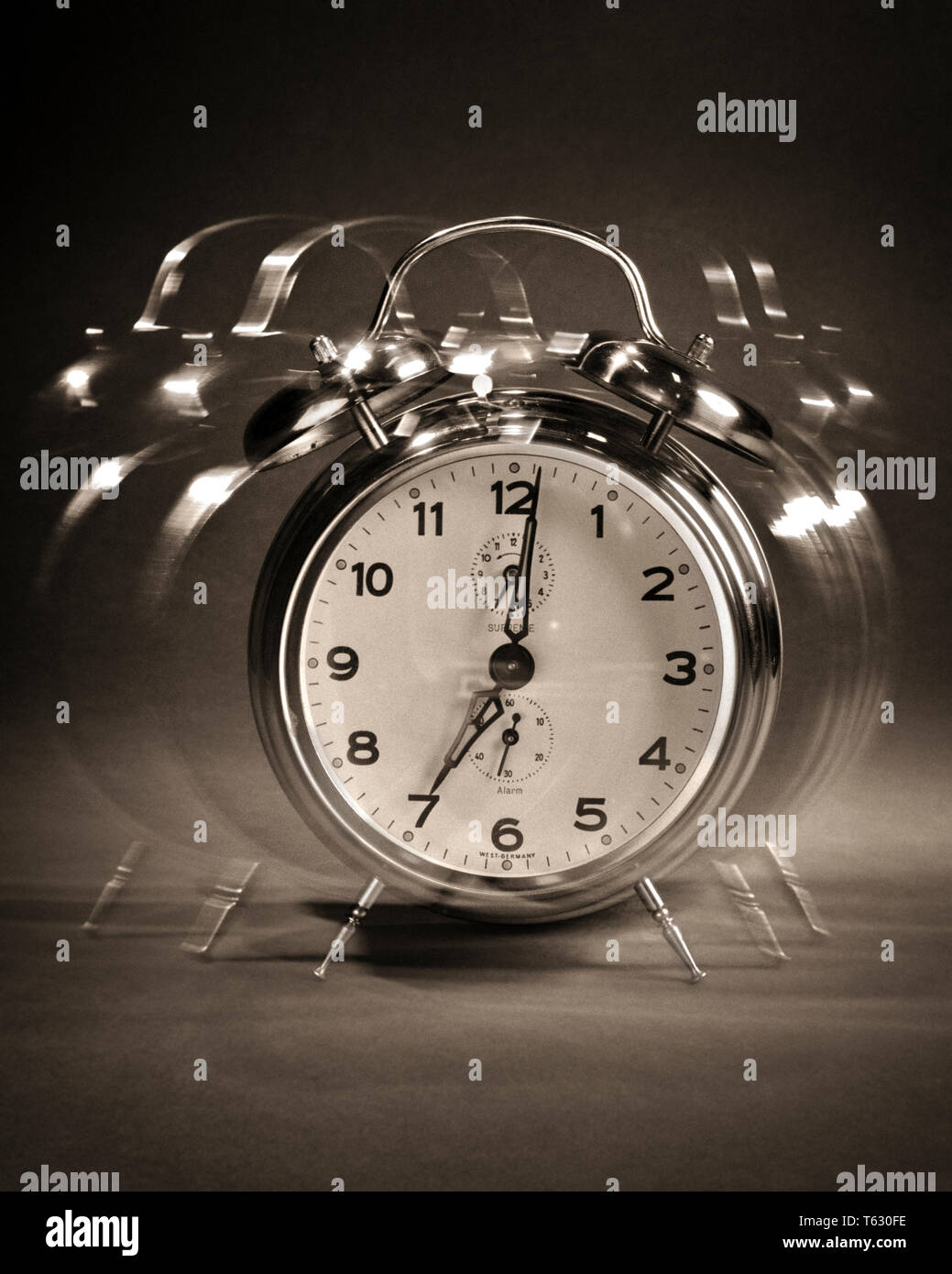 1960s RINGING MOVING SHAKING ALARM CLOCK AT 7 O'CLOCK AM MORNING WAKE-UP - s14120 HAR001 HARS AM GET UP O'CLOCK SYMBOLIC WINDUP CONCEPTS WAKEN BLACK AND WHITE GRAPHIC EFFECT HAR001 OLD FASHIONED REPRESENTATION - Stock Image