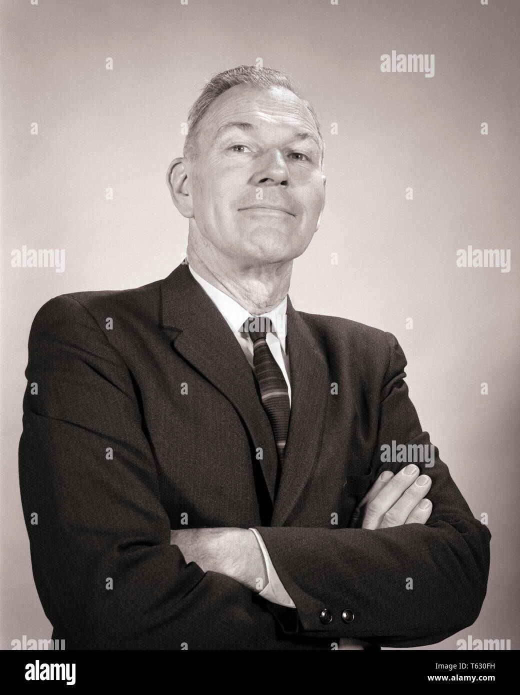 1960s MATURE MAN ARMS CROSSED FOLDED WITH SELF-SATISFIED SMUG SUPERIOR FACIAL EXPRESSION LOOKING AT CAMERA - s14663 HAR001 HARS POLITICIAN PRIDE SUPERIOR POLITICS SALESMEN BLACK AND WHITE CAUCASIAN ETHNICITY HAR001 OLD FASHIONED SELF-SATISFIED - Stock Image