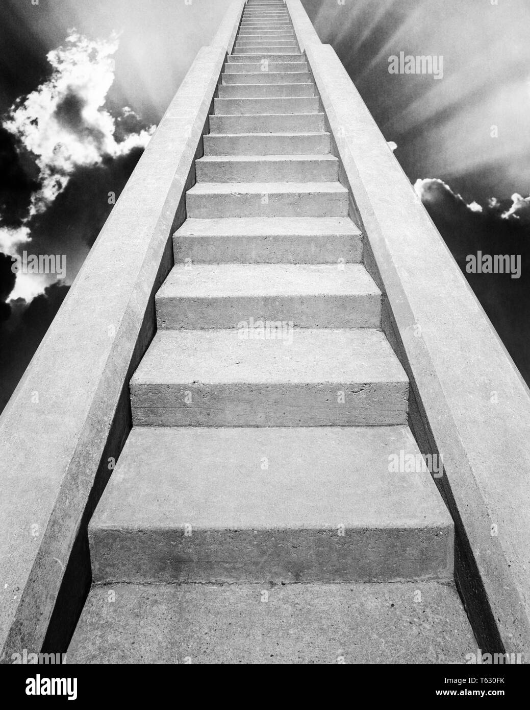 1960s VIEW AT BOTTOM OF SET OF CONCRETE STAIRS  LOOKING UP TO THE TOP INTO SKY WITH GOD RAYS LIGHT STAIRWAY TO HEAVEN PARADISE - s14723a HAR001 HARS CHOICE COMPOSITE EXTERIOR LOW ANGLE RAYS STAIR DIRECTION GOD RAYS HEAVEN UP STAIRCASE STAIRWAY CONCEPT CONNECTION CONCEPTUAL STILL LIFE PARADISE STEEP STYLISH FAITHFUL SYMBOLIC CONCEPTS FAITH IDEAS LOOKING  UP REWARD BELIEF BLACK AND WHITE CONCRETE HAR001 OLD FASHIONED REPRESENTATION SUN RAYS - Stock Image