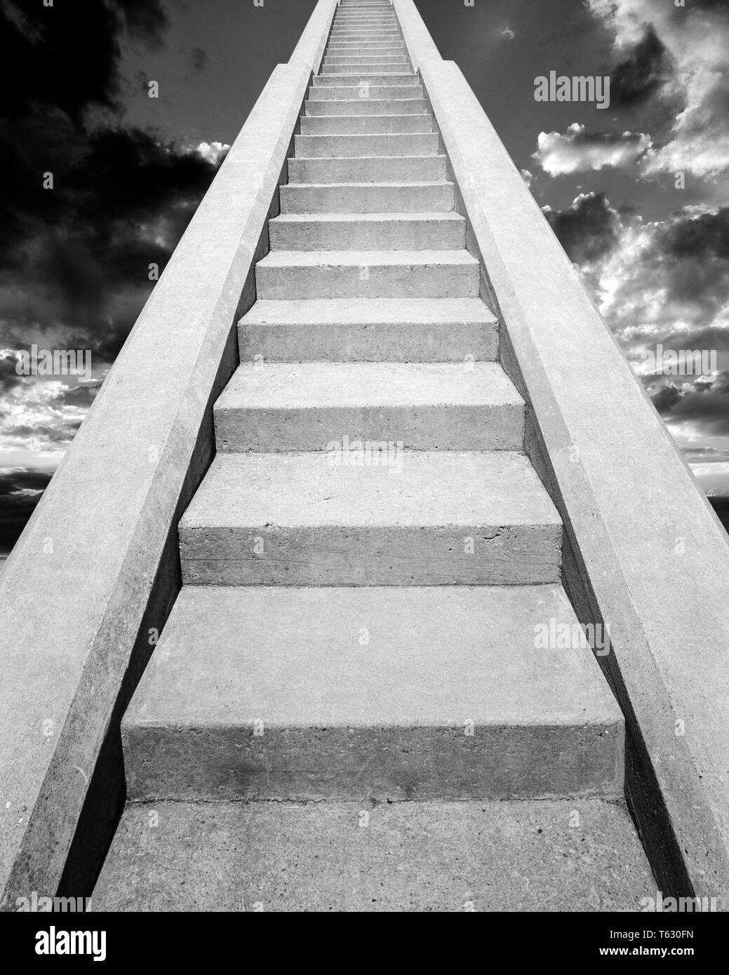 VIEW AT BOTTOM OF SET OF CONCRETE STAIRS  LOOKING UP TO THE TOP INTO THE SKY THE HEAVENS - s14723c HAR001 HARS CHOICE COMPOSITE EXTERIOR LOW ANGLE STAIR DIRECTION HEAVEN UP STAIRCASE STAIRWAY CONCEPT CONNECTION CONCEPTUAL STILL LIFE PARADISE STEEP STYLISH FAITHFUL SYMBOLIC CONCEPTS FAITH IDEAS LOOKING  UP REWARD BELIEF BLACK AND WHITE CONCRETE HAR001 OLD FASHIONED REPRESENTATION - Stock Image
