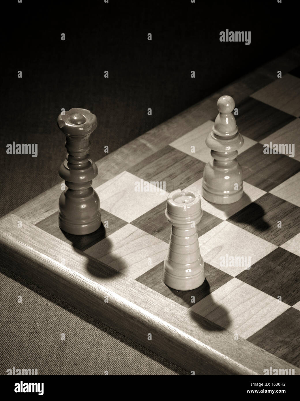 1960s CHECKMATE THREE CHESS PIECES SHOW OPPOSING BLACK KING HELD IN CHECK THREATENED WITH CAPTURE BY THE WHITE BISHOP AND ROOK - s15260 HAR001 HARS THREATENED ESCAPE ROOK SYMBOLIC CHECKMATE CONCEPTS OPPOSING SOLUTIONS BISHOP BLACK AND WHITE CAPTURE HAR001 OLD FASHIONED PERSONIFICATION REPRESENTATION - Stock Image