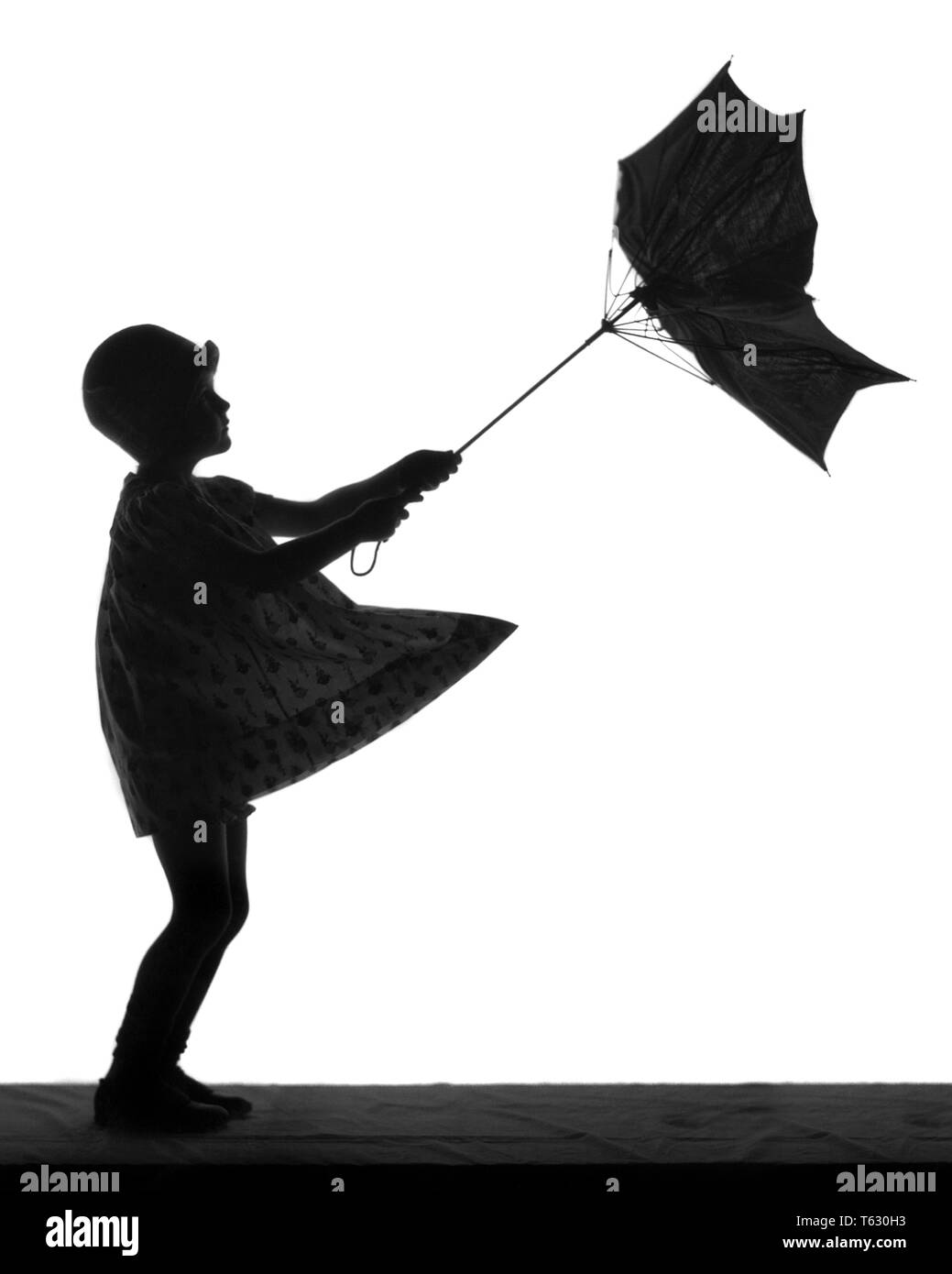 1920s ANONYMOUS SILHOUETTE OF LITTLE GIRL WITH UMBRELLA TURNED INSIDE OUT IN THE WIND - s1689 HAR001 HARS OUTLINE SADNESS SILHOUETTED EXCITEMENT TURNED LITTLE GIRL CONCEPTUAL STYLISH WINDY CLOCHE HAT ANONYMOUS BAD WEATHER GUSTY INSIDE OUT JUVENILES BLACK AND WHITE HAR001 OLD FASHIONED - Stock Image