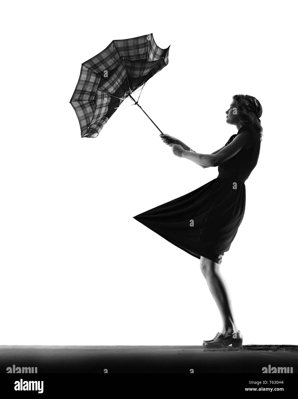 1930s 1940s ANONYMOUS SILHOUETTE OF TEENAGE  GIRL WITH UMBRELLA TURNED INSIDE OUT IN THE WIND - s1702 HAR001 HARS BALANCE TROUBLE LIFESTYLE FEMALES STUDIO SHOT NATURE COPY SPACE FULL-LENGTH RAINY PERSONS CUTOUT RISK TEENAGE GIRL SILHOUETTES STORMY B&W OUTLINE SADNESS SILHOUETTED EXCITEMENT TURNED LITTLE GIRL CONCEPTUAL STYLISH TEENAGED WINDY CLOCHE HAT ANONYMOUS BAD WEATHER GUSTY INSIDE OUT JUVENILES YOUNG ADULT WOMAN BLACK AND WHITE HAR001 OLD FASHIONED - Stock Image