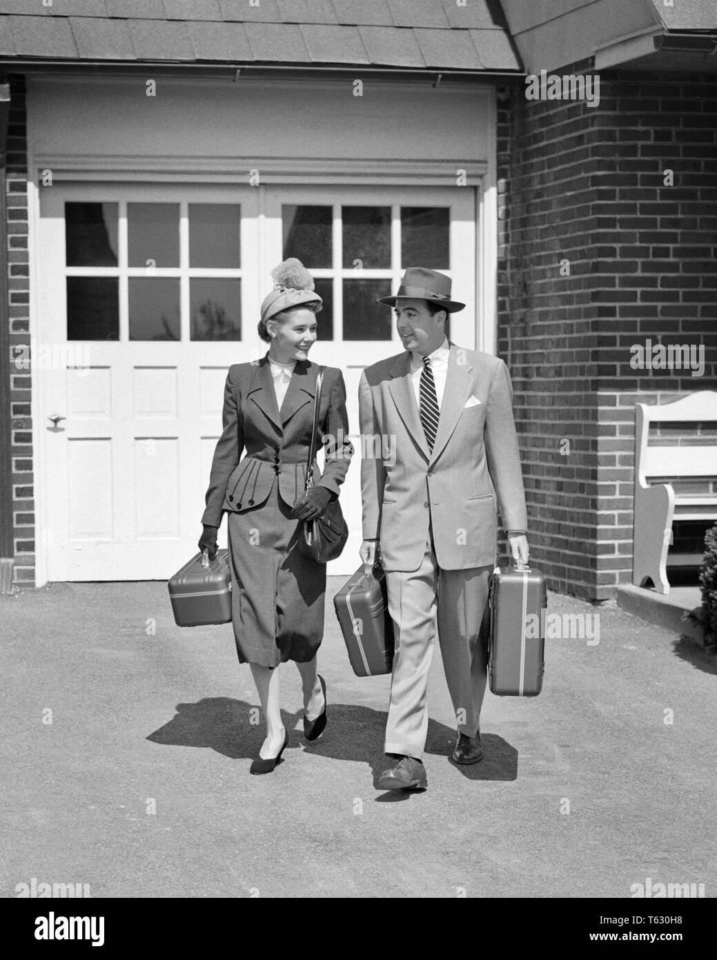 1950s COUPLE FASHIONABLY DRESSED WALKING DOWN DRIVEWAY CARRYING LUGGAGE - s177 HAR001 HARS FEMALES MARRIED SPOUSE HUSBANDS HEALTHINESS HOME LIFE COPY SPACE FRIENDSHIP FULL-LENGTH LADIES PERSONS MALES B&W PARTNER SUIT AND TIE HAPPINESS ADVENTURE LEISURE STYLES TRIP EXCITEMENT CONNECTION FASHIONABLY STYLISH COOPERATION FASHIONS MID-ADULT MID-ADULT MAN MID-ADULT WOMAN TOGETHERNESS WIVES BLACK AND WHITE CAUCASIAN ETHNICITY HAR001 OLD FASHIONED - Stock Image