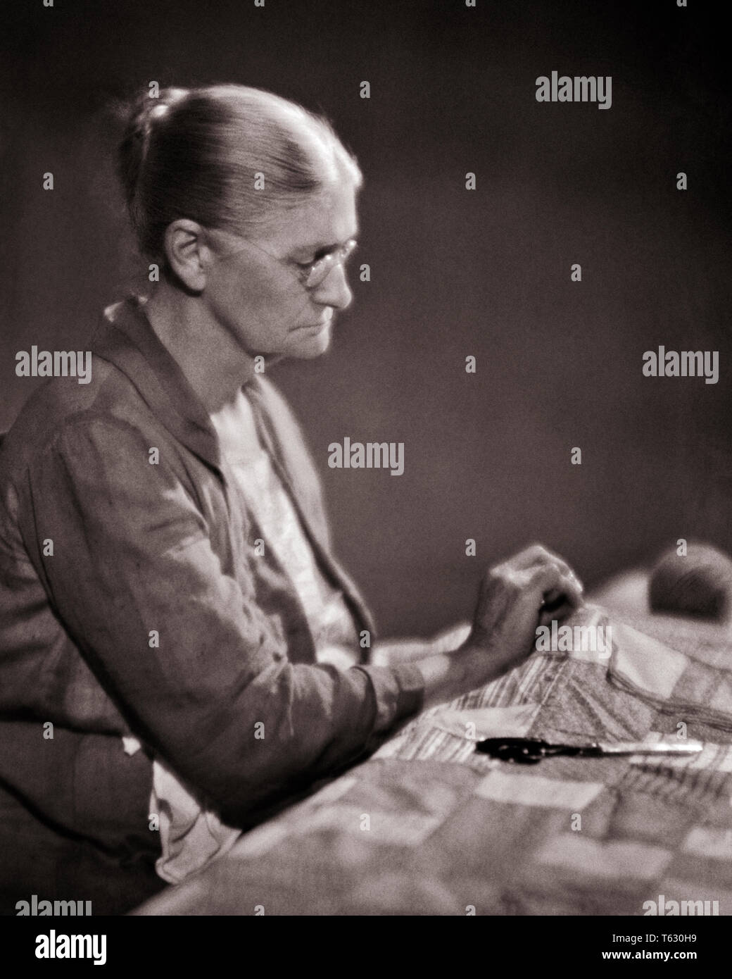 1930s ELDERLY WOMAN SEWING WORKING ON A PATCHWORK QUILT WEARING EYEGLASSES FOCUSED ON HER HAND WORK - s17446 HAR001 HARS SKILLS OLDSTERS OLDSTER PATCHWORK ELDERS NEEDLEWORK SEAMSTRESS QUILTING CREATE CREATIVITY ELDERLY WOMAN FOCUSED QUILT BLACK AND WHITE CAUCASIAN ETHNICITY HANDMADE HAR001 OLD FASHIONED - Stock Image
