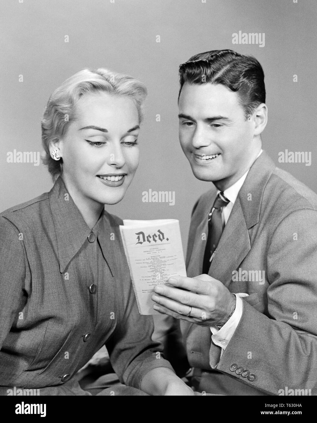 1950s BRUNETTE MAN AND BLONDE WOMAN SMILING TOGETHER LOOKING AT THE DEED TO THEIR PROPERTY - s1851 HAR001 HARS SPOUSE HUSBANDS HOME LIFE COPY SPACE HALF-LENGTH LADIES PERSONS INSPIRATION MALES FOLDER B&W PARTNER BRUNETTE FREEDOM GOALS SUCCESS DREAMS HAPPINESS ADVENTURE BROCHURE PROPERTY THEIR STRATEGY AND EXCITEMENT PRIDE THE TO CONCEPTUAL INVESTMENT STYLISH OWNERS LOOKING AT DEED MID-ADULT MID-ADULT MAN MID-ADULT WOMAN OWNERSHIP TOGETHERNESS WIVES BLACK AND WHITE CAUCASIAN ETHNICITY HAR001 OLD FASHIONED - Stock Image