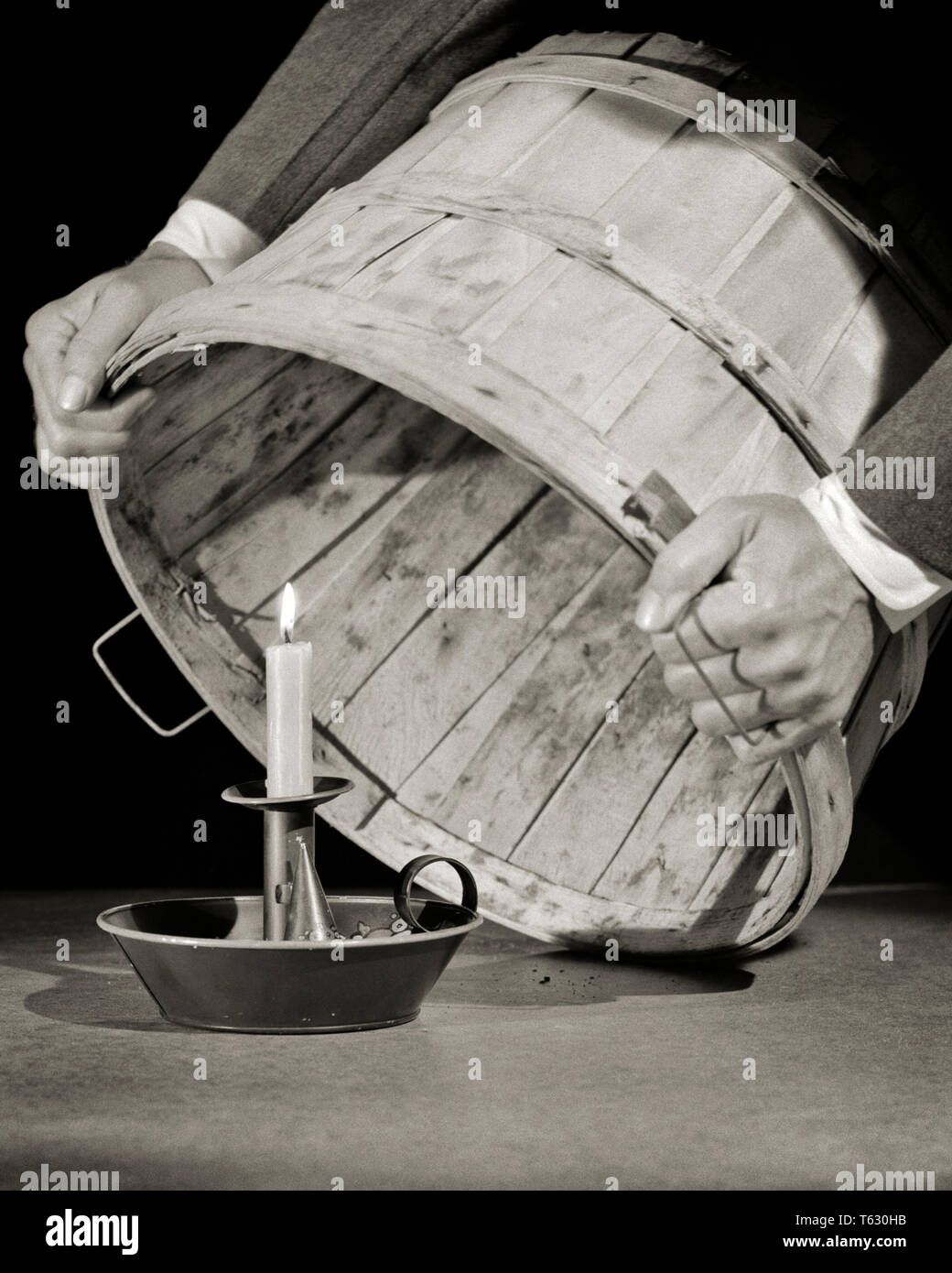 1940s MAN PUTTING A BUSHEL BASKET OVER A LIT CANDLE Do not conceal your talents or abilities DO NOT HIDE YOUR FAITH  - s2000 HAR001 HARS PARABLE CONCEAL FAITHFUL MAXIM OR SYMBOLIC CONCEPTS CREATIVITY FAITH MID-ADULT MID-ADULT MAN SCRIPTURE SPIRITUAL TALENTS BELIEF BLACK AND WHITE CAUCASIAN ETHNICITY HANDS ONLY HAR001 INSPIRATIONAL OLD FASHIONED REPRESENTATION - Stock Image