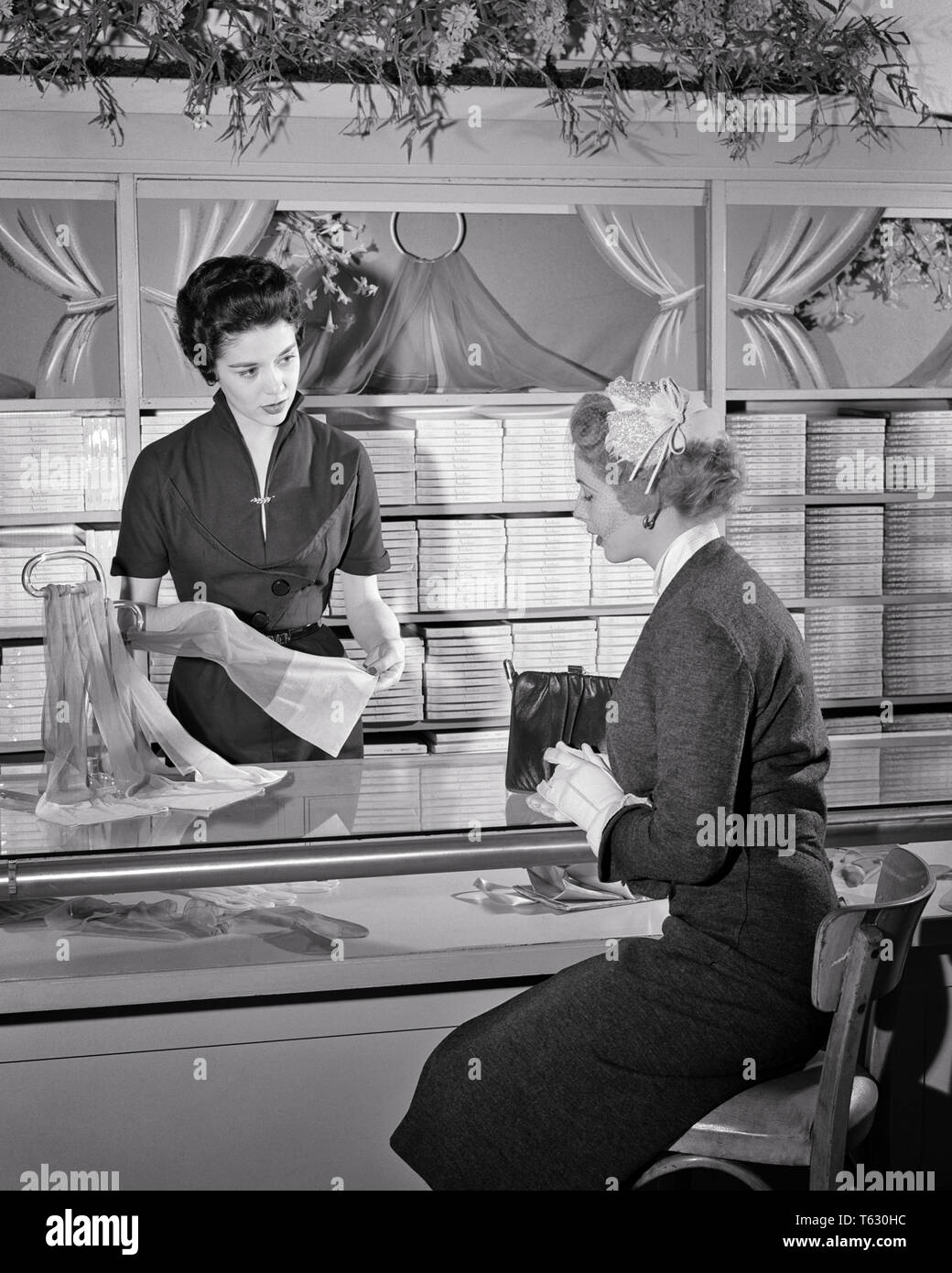 1950s Saleswoman Helping A Woman Seated At The Hosiery Counter Of Department Store S2367 Har001 Hars Style Communication Career Young Adult Information Department Lifestyle Satisfaction Females Jobs Showing Luxury Seated Copy