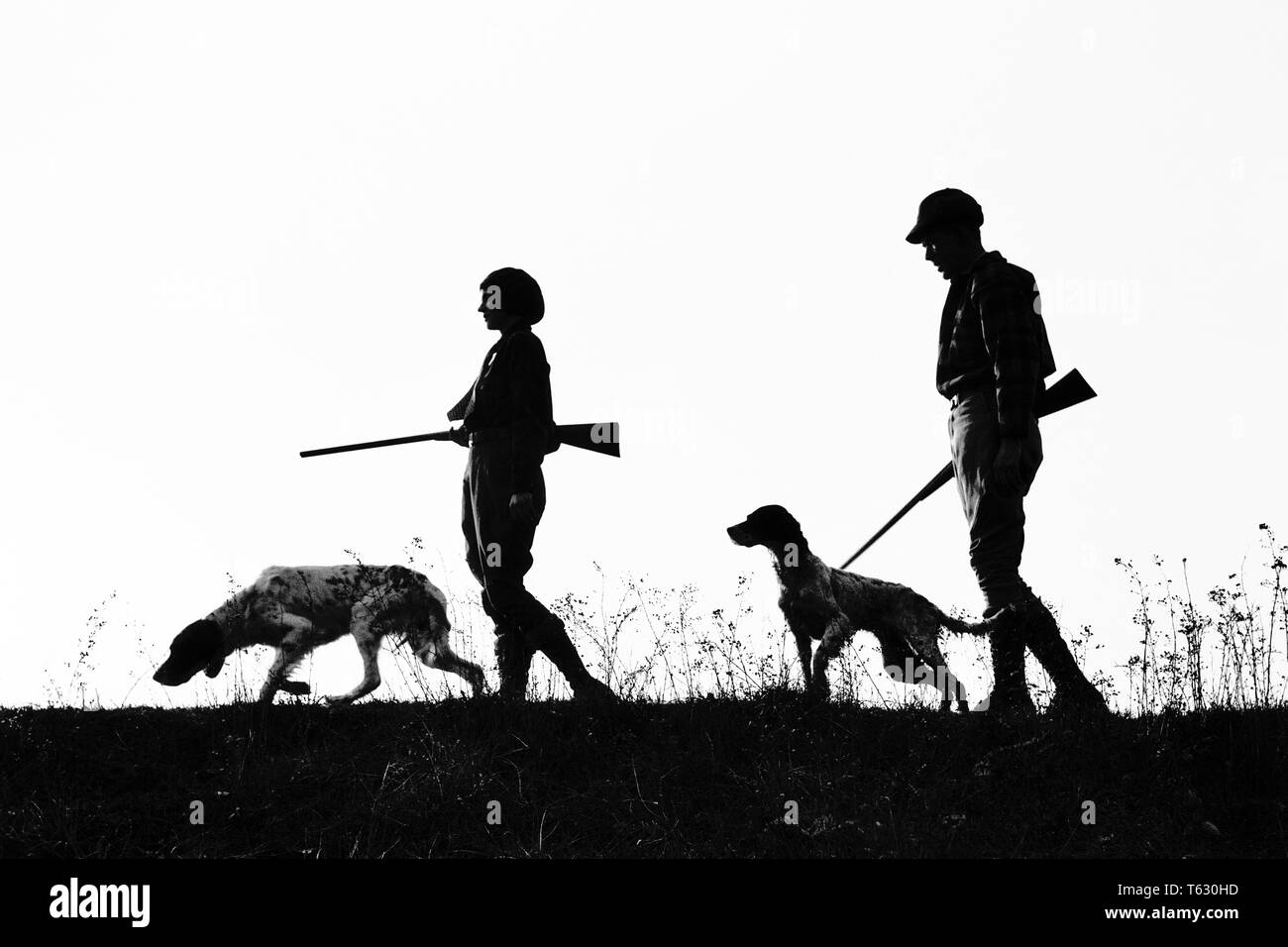 1920s 1930s ANONYMOUS SILHOUETTE MAN AND WOMAN HUNTERS CARRYING GUNS EACH WITH A HUNTING DOG  - s2541 HAR001 HARS LEISURE SILHOUETTED AND CANINES RECREATION POOCH CONNECTION ANONYMOUS CANINE COOPERATION FIREARM FIREARMS HUNTERS MAMMAL MID-ADULT MID-ADULT MAN MID-ADULT WOMAN TOGETHERNESS BLACK AND WHITE HAR001 OLD FASHIONED - Stock Image