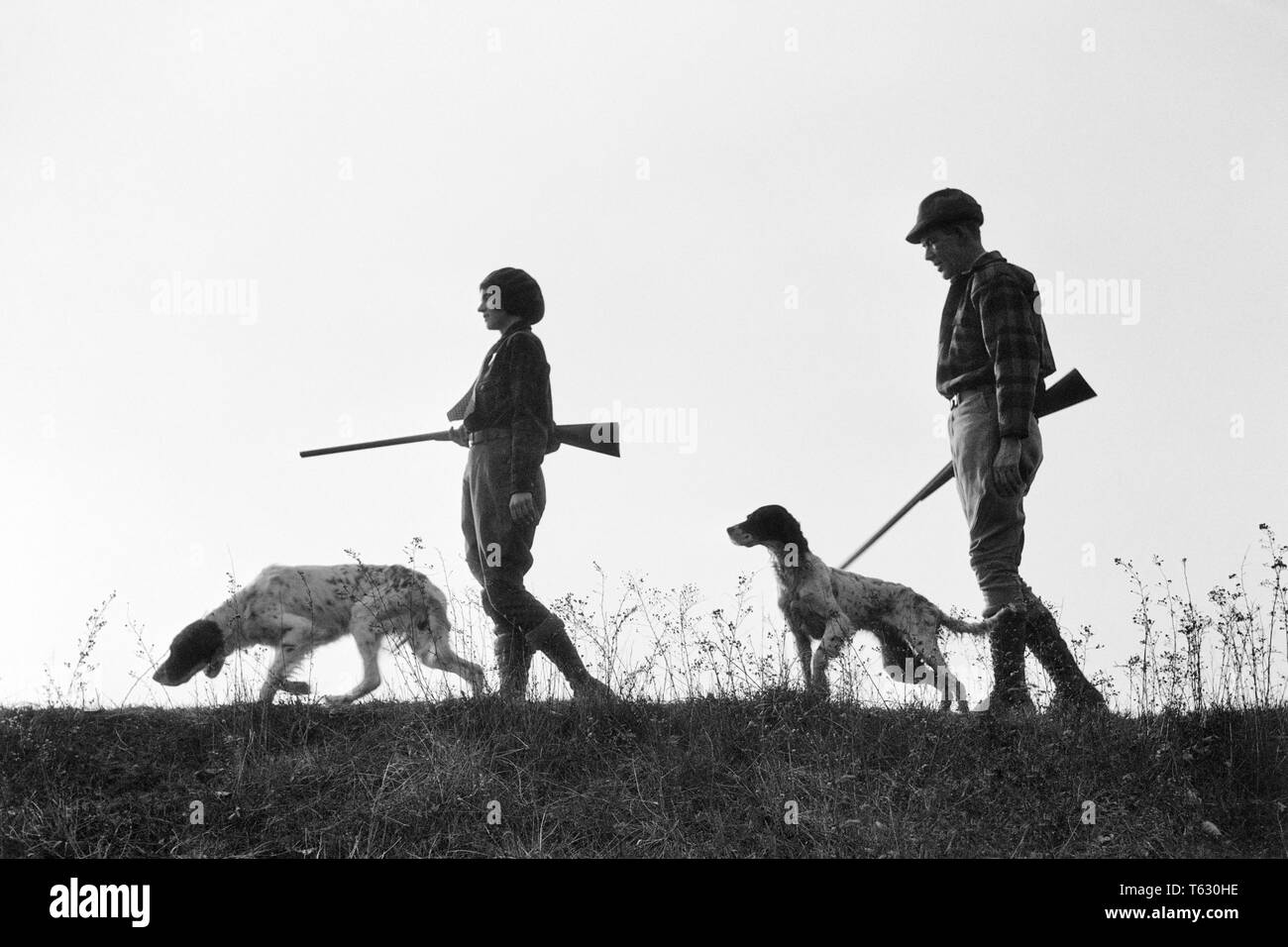 1920s 1930s ANONYMOUS SILHOUETTE MAN AND WOMAN HUNTERS CARRYING GUNS EACH WITH A HUNTING DOG  - s2541a HAR001 HARS LEISURE SILHOUETTED AND CANINES RECREATION POOCH CONNECTION ANONYMOUS CANINE COOPERATION FIREARM FIREARMS HUNTERS MAMMAL MID-ADULT MID-ADULT MAN MID-ADULT WOMAN TOGETHERNESS BLACK AND WHITE HAR001 OLD FASHIONED - Stock Image